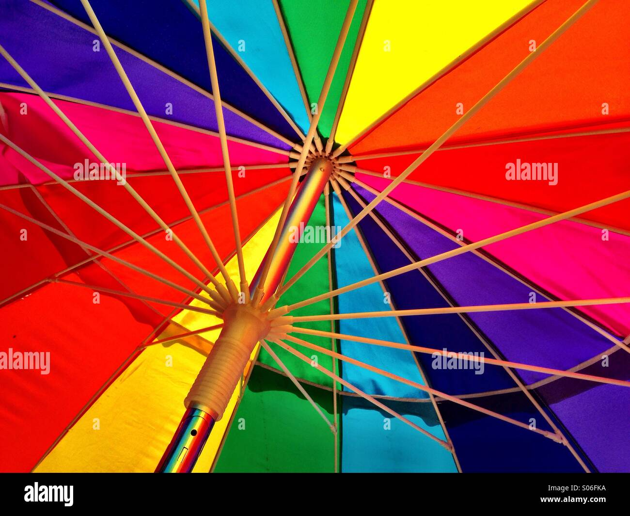 A rainbow-colored umbrella glows in the sun. - Stock Image