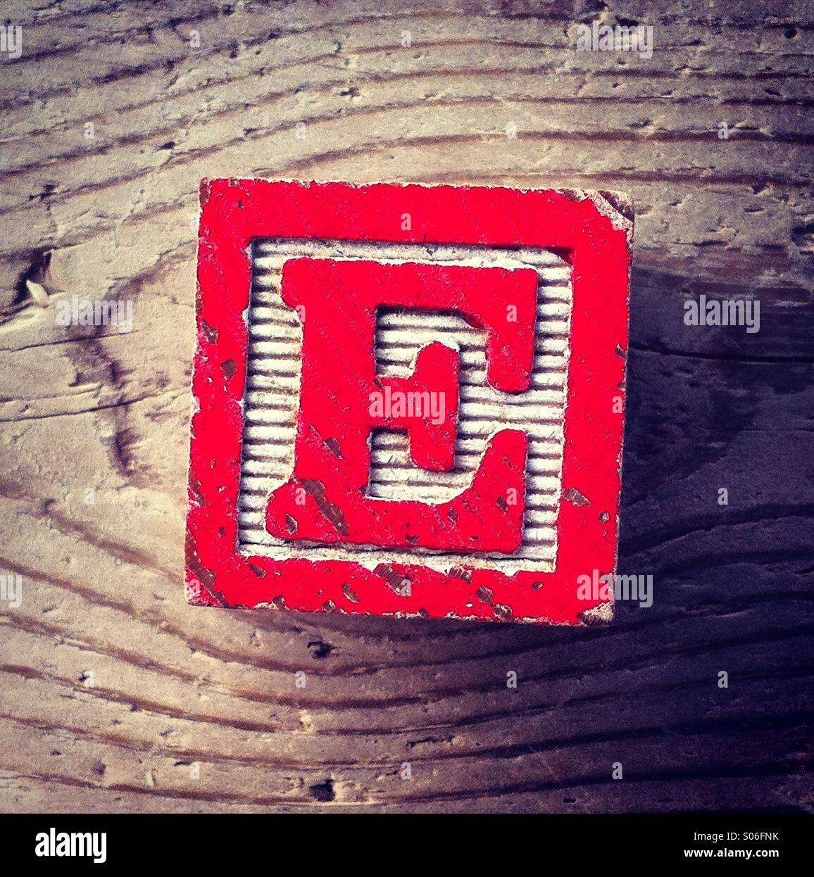 It's a woodblock toy with an alphabet letter on it: E - Stock Image