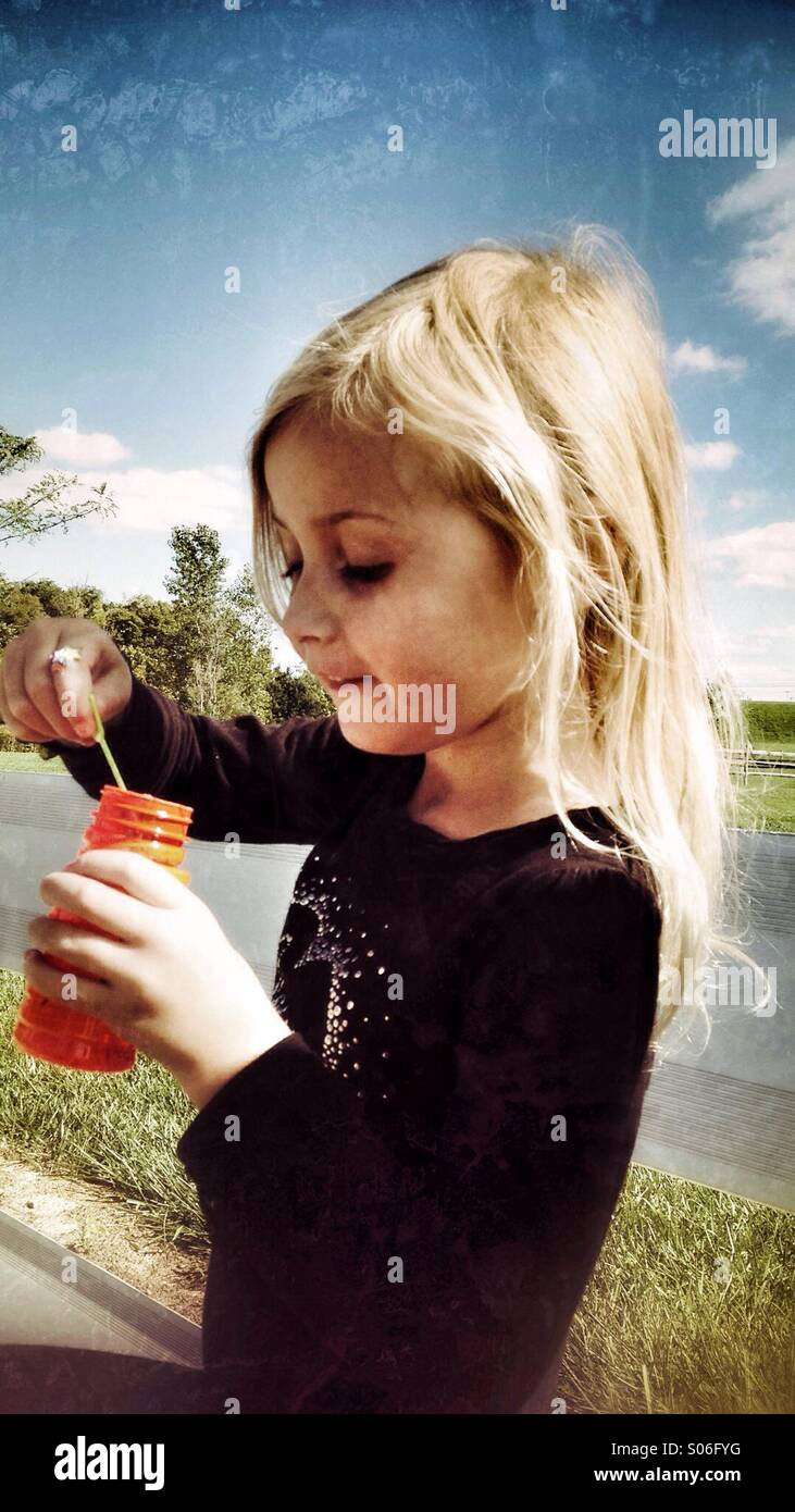 A girl filling a bubble wand with soap bubbles. - Stock Image