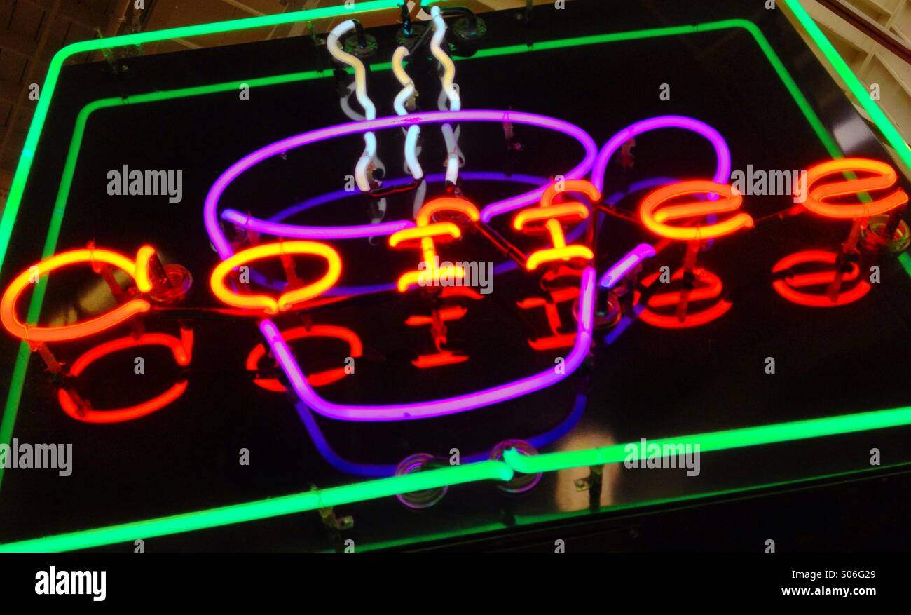 Neon sign for coffee. Includes a purple neon cup, white neon steam, warm orange and red neon word 'coffee' - Stock Image