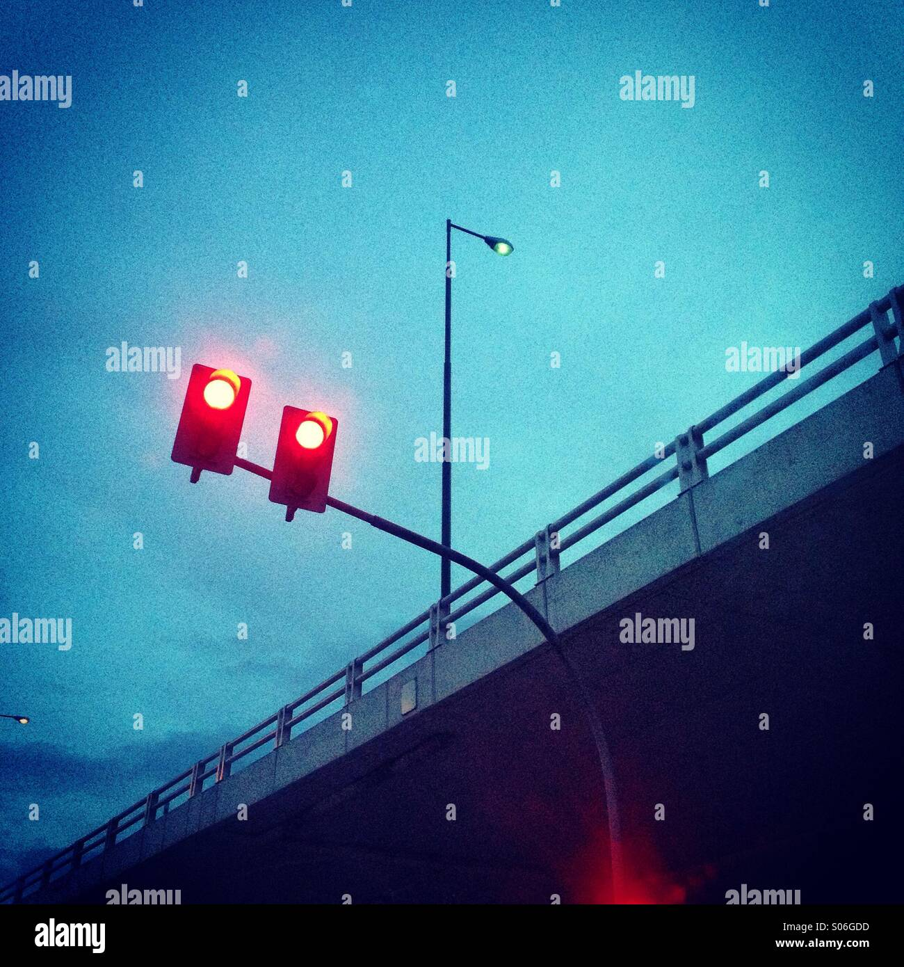 Red lights beneath overpass - Stock Image