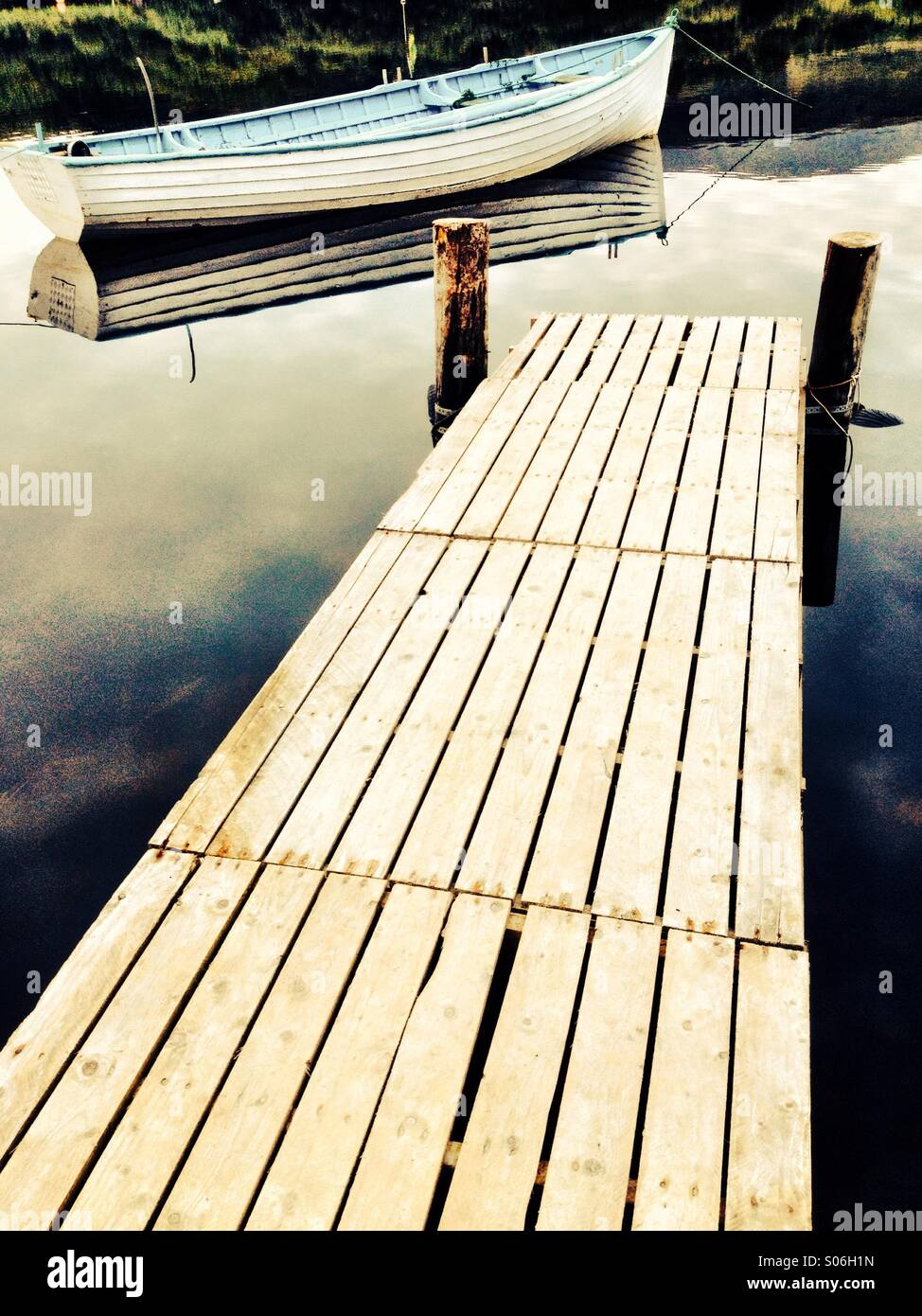 Wooden Jetty and Boat - Stock Image