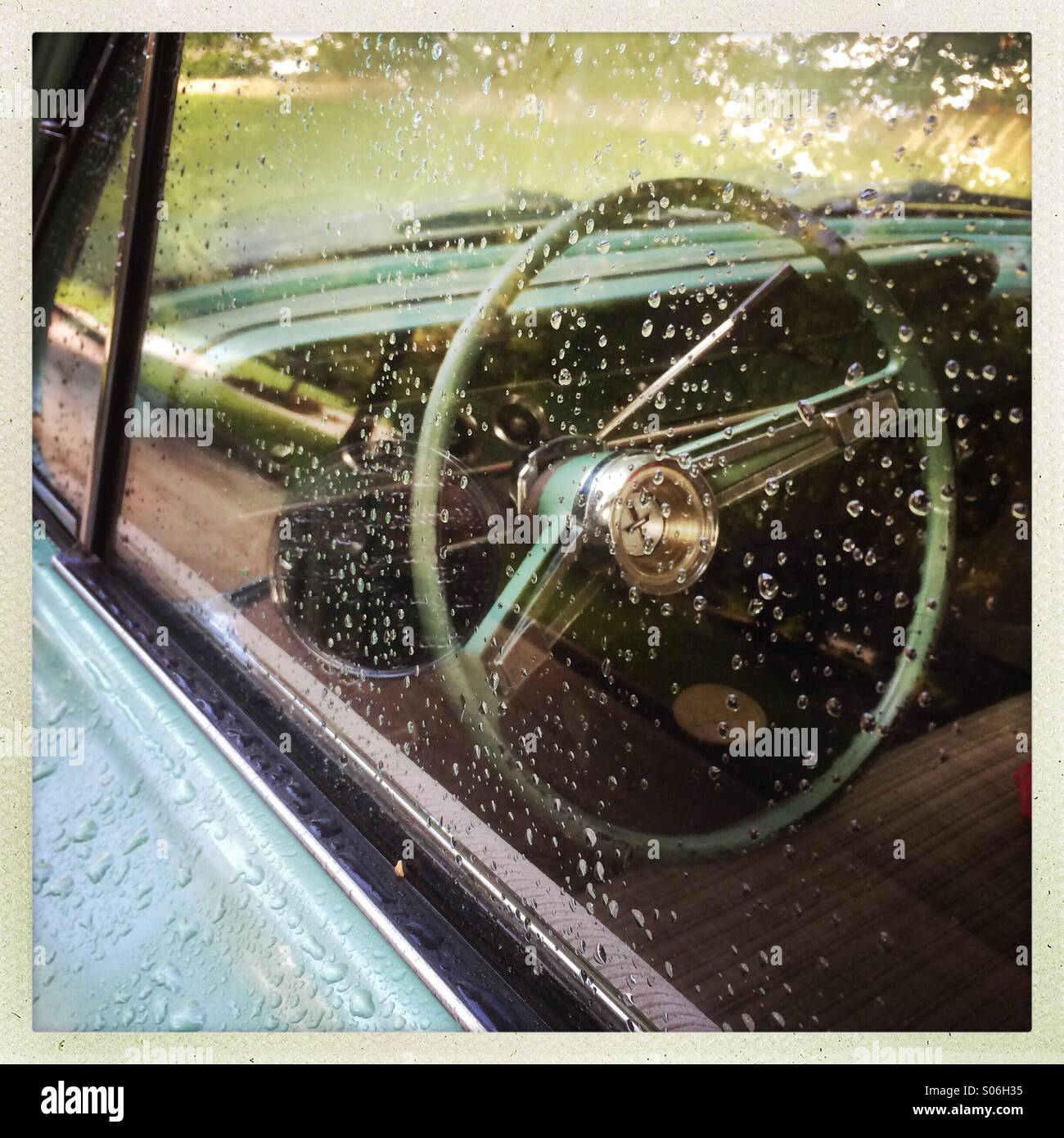 Rainy, vintage, car window with view of steering wheel - Stock Image