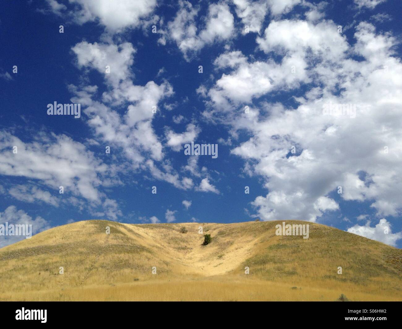 Blue sky and whispy clouds above the hills along the Wasatch a Mountains of Salt Lake City, UT. Stock Photo