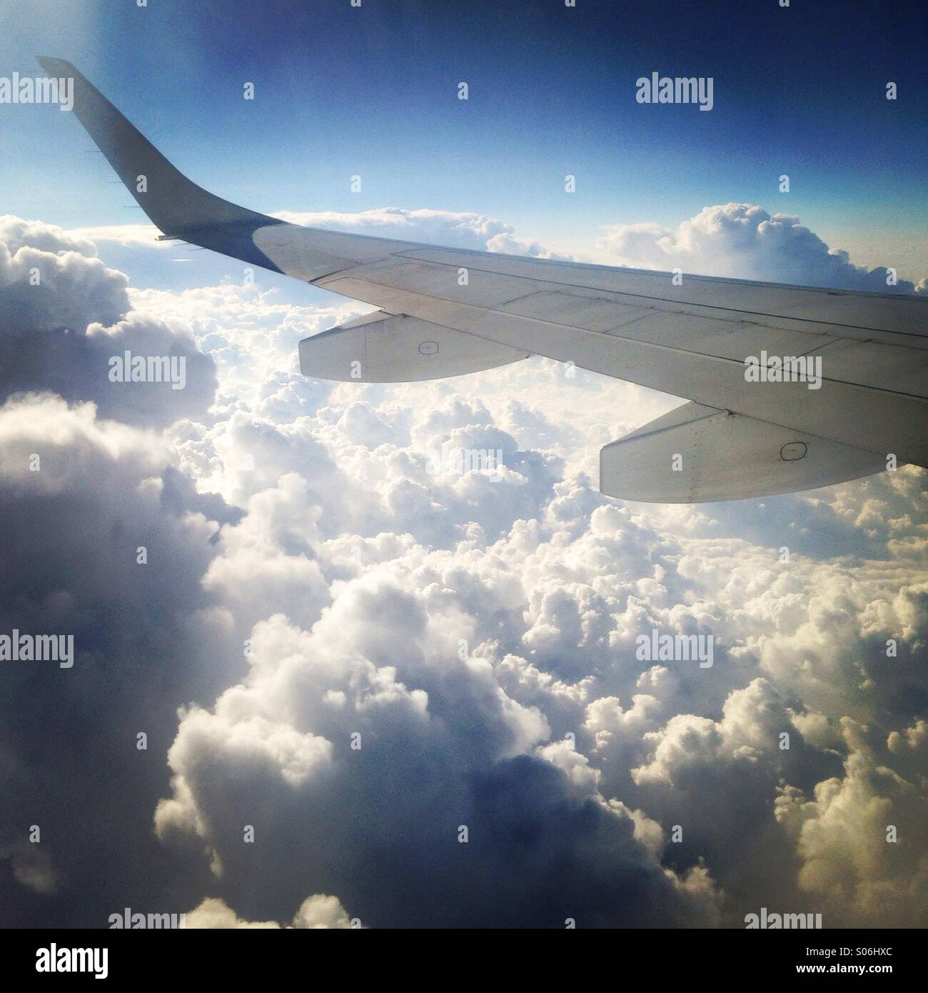 An airplane wing as it flys over fluffy clouds. Traveling through Europe. - Stock Image