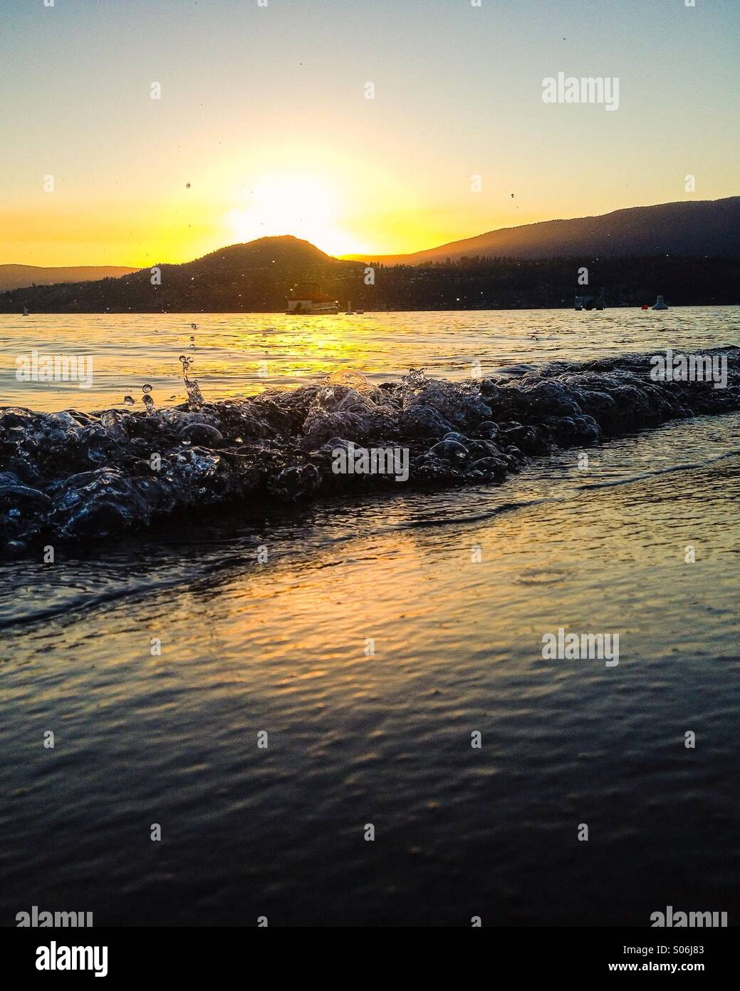 Small waves breaking on the beach at sunset; the glistening water bubbles and splashes. - Stock Image
