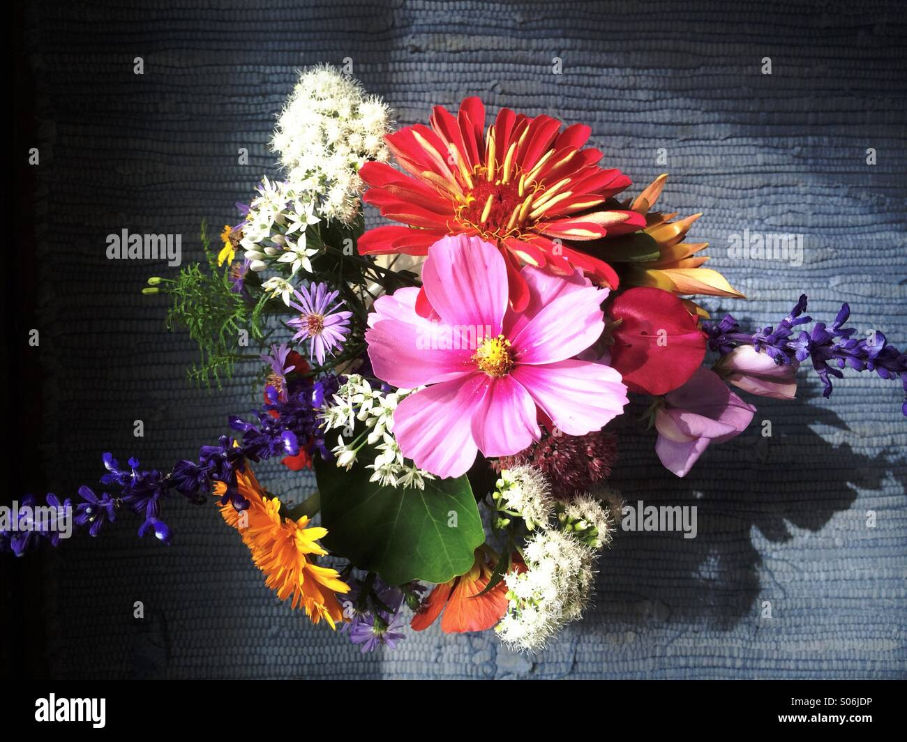 Late summer bouquet of cosmos, zinnia, dahlia, calendula, asters, marigolds, garlic chives, sweet pea, Victoria - Stock Image