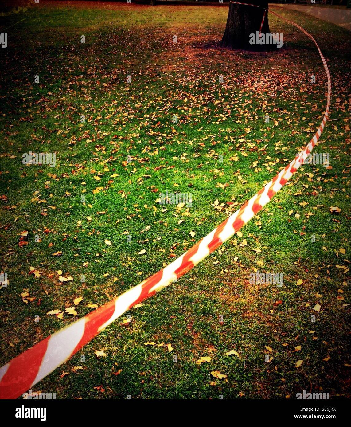 Red and white market tape blowing in wind - Stock Image