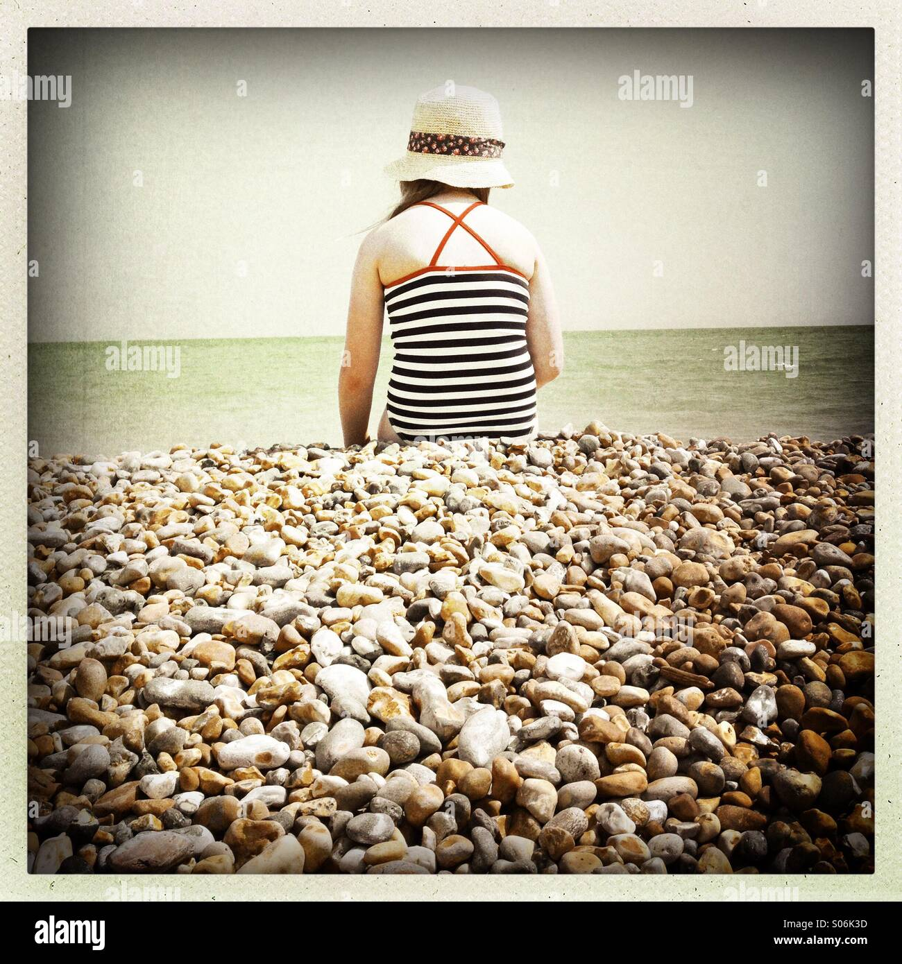 Girl In Hat, Sitting On Pebbled Beach - Stock Image