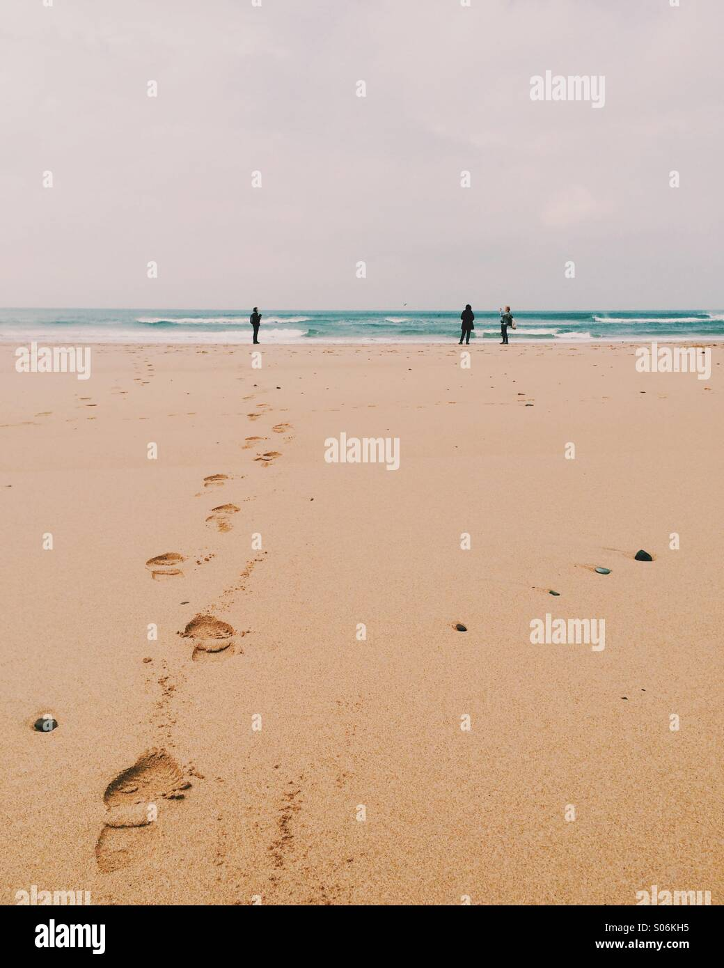 Three people on a beach - Stock Image