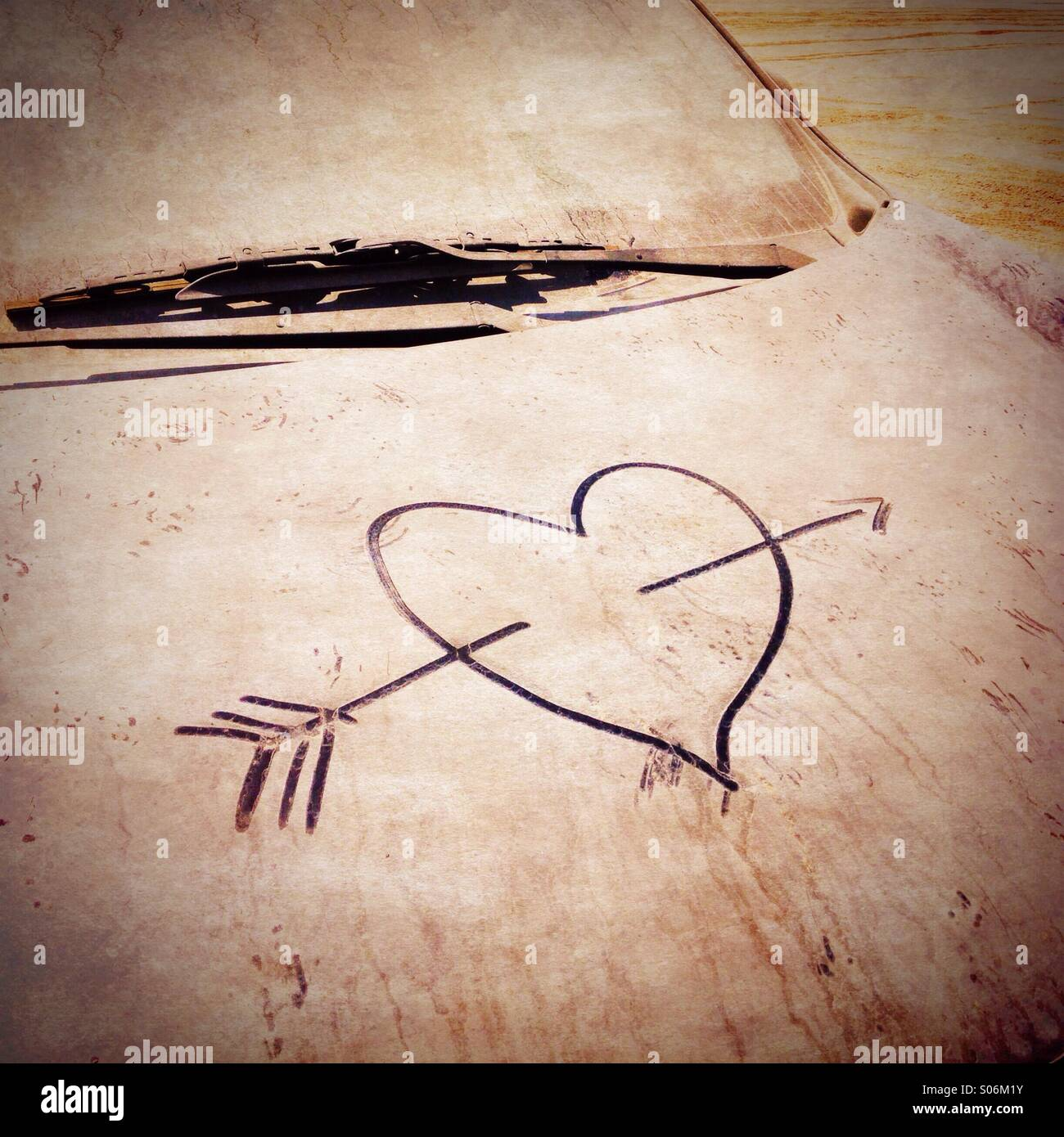 Love heart drawn onto dirty abandoned car covered in sand in parking lot in Dubai UAE - Stock Image