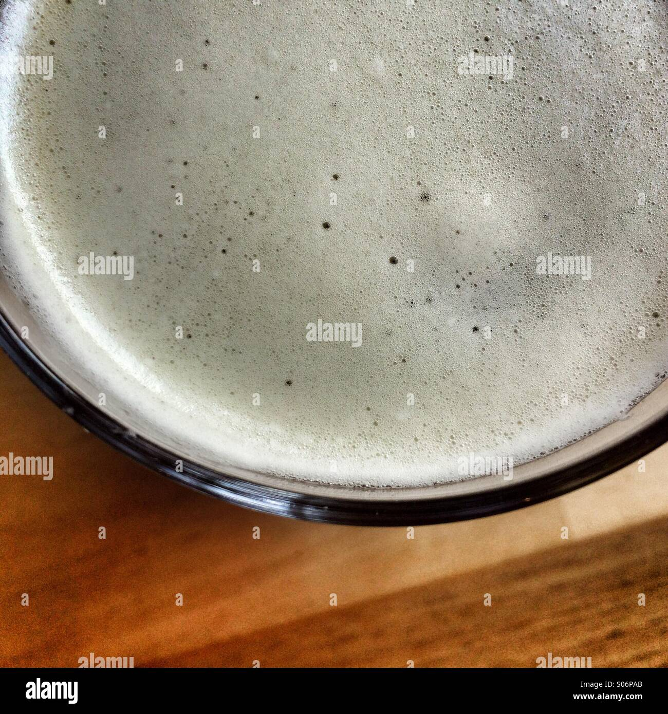 View looking down onto pint beer glass showing frothy bubbles - Stock Image
