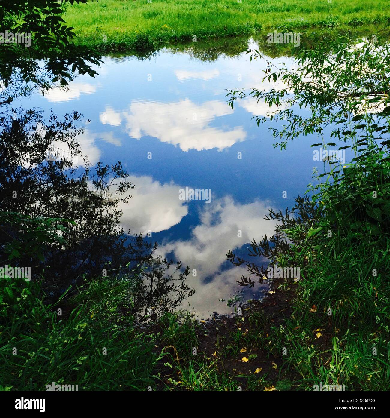 Idyllic summer scene with white clouds reflected in river. - Stock Image