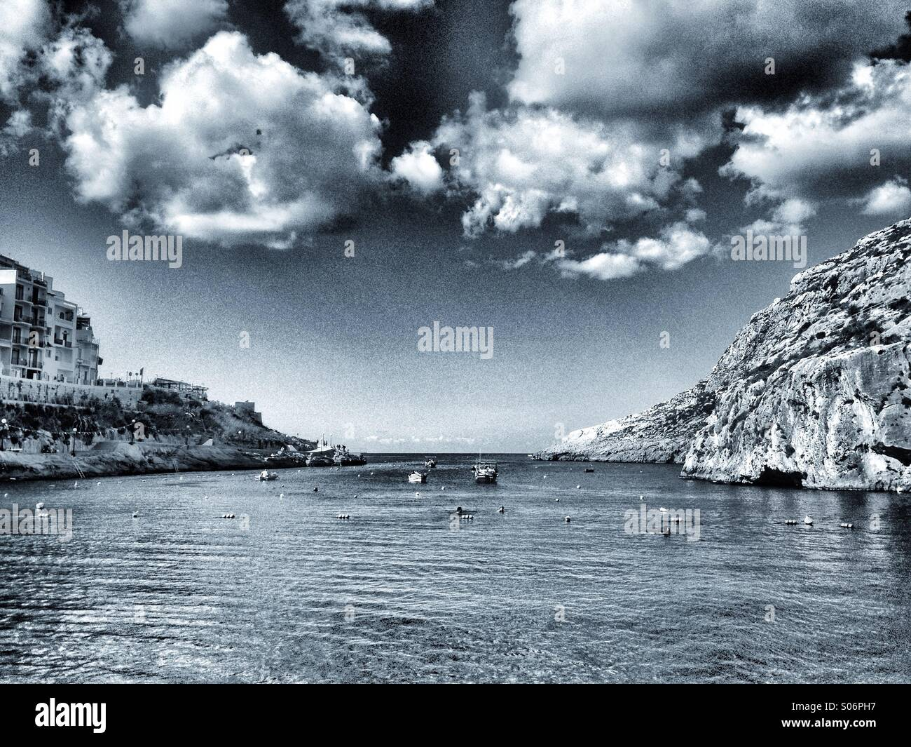 Sunny harbour with fresh autumnal clouds in toned monochrome - Stock Image