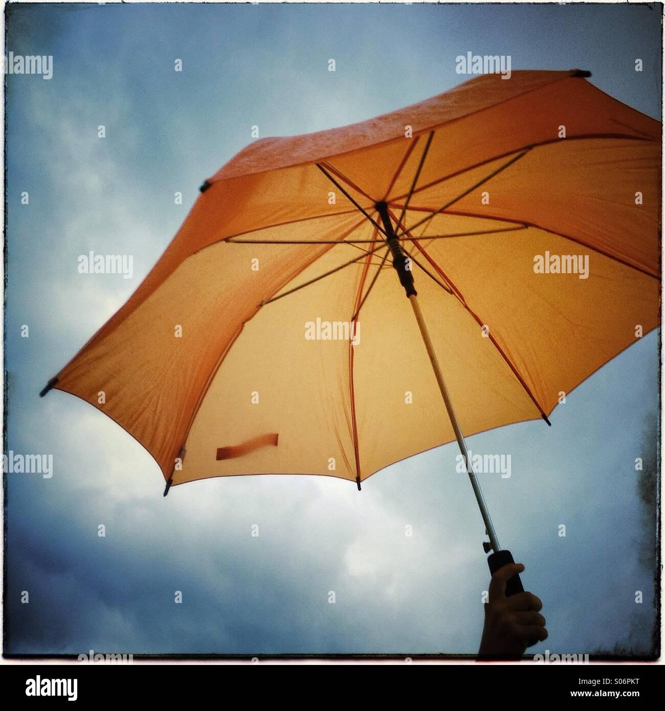 Open orange umbrella isolated on cloudy sky background - Stock Image