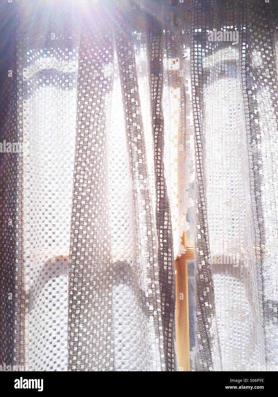 Lace curtains across a window with streaming sunlight. - Stock Image