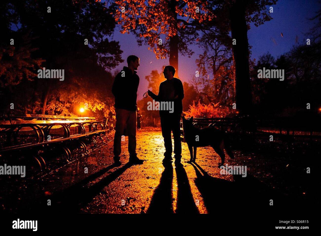 Two men converse on a New York City autumn night at strawberry fields in Central Park. - Stock Image