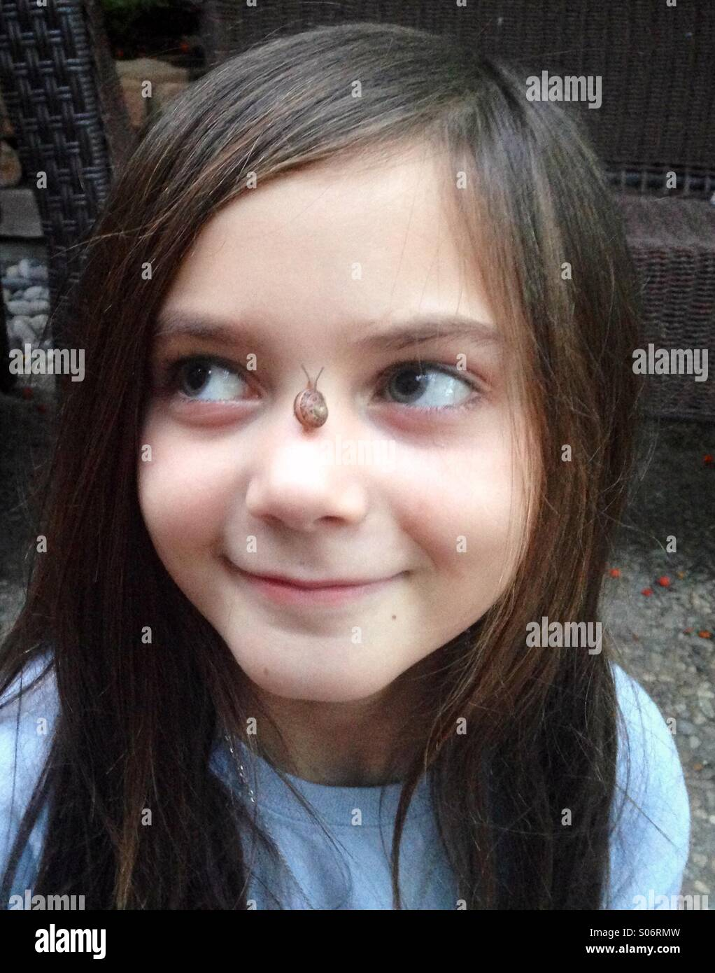 A young adorable girl smiles with a small snail on her nose. - Stock Image