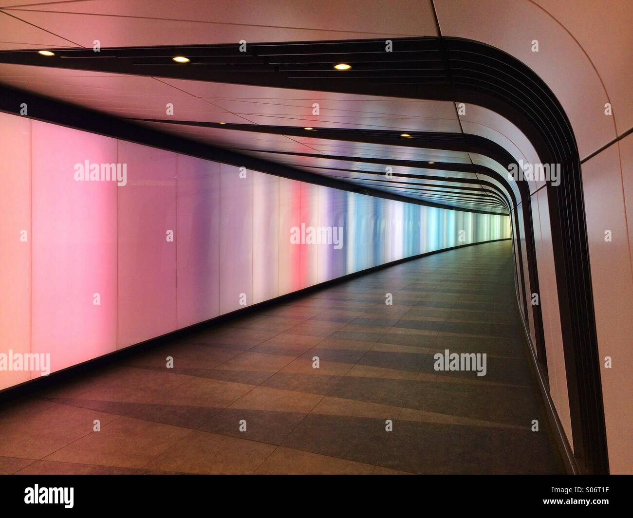 A tunnel at Kings Cross Station with changing lights. Stock Photo