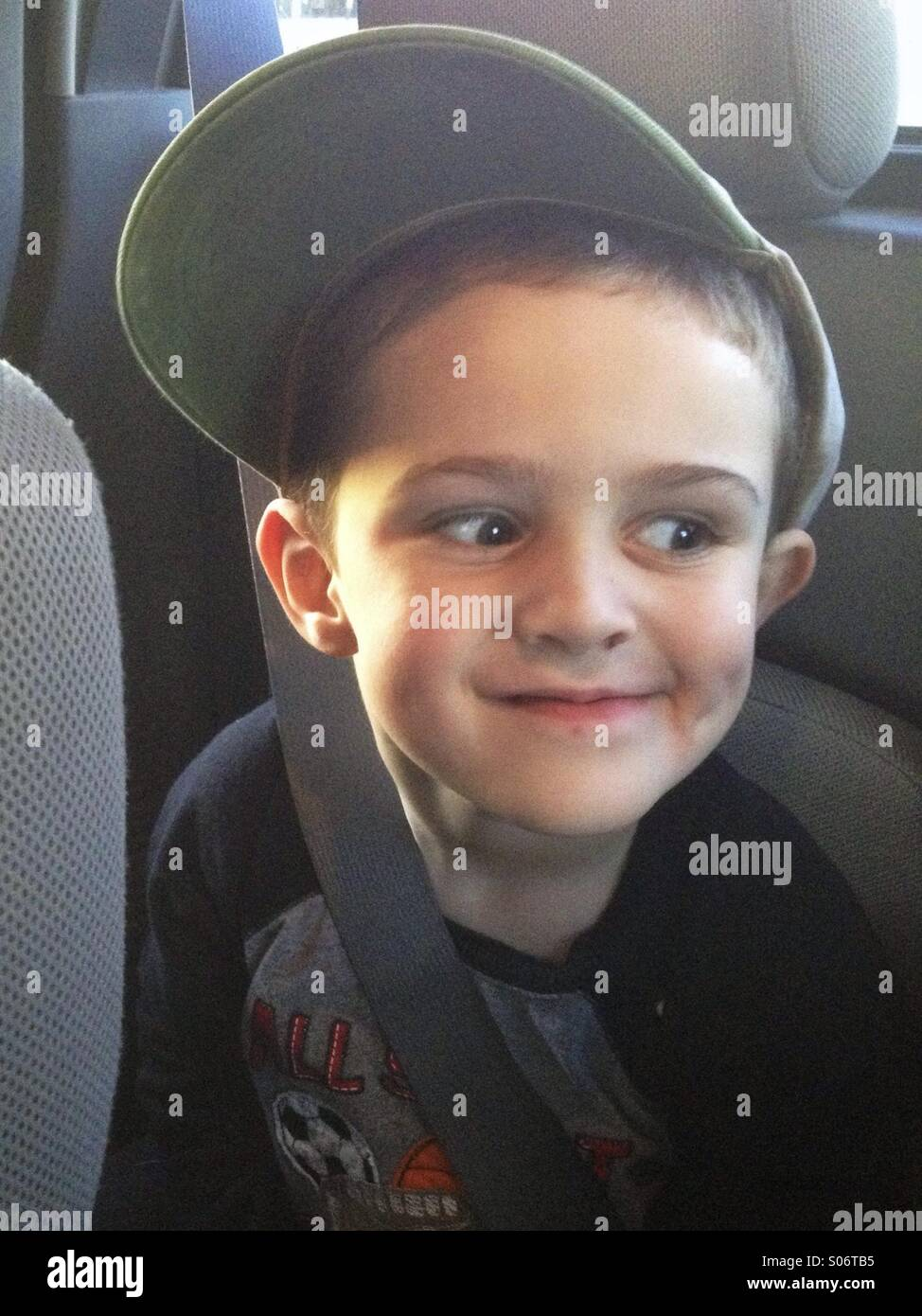 A three year old boy wearing a mans cap and looking mischievous. - Stock Image