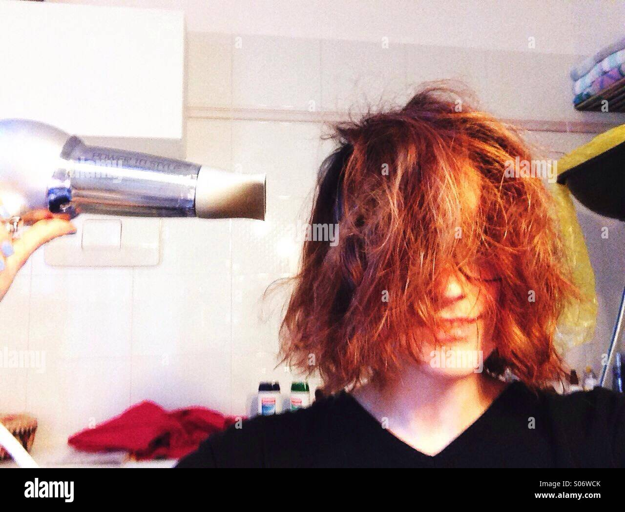 Girl blow drying her hair - Stock Image