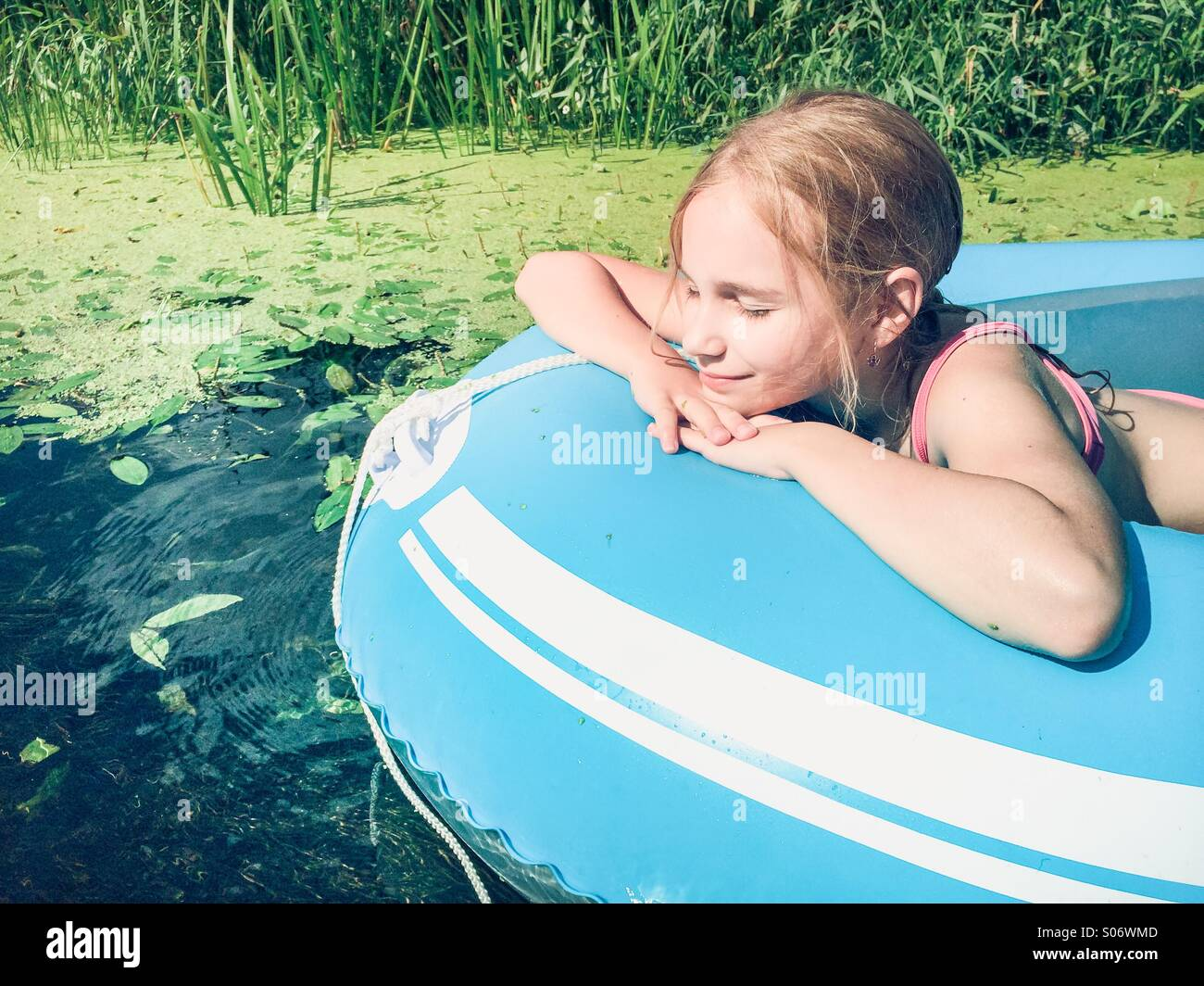 Little girl sitting in a raft on a river with lush greenery - Stock Image