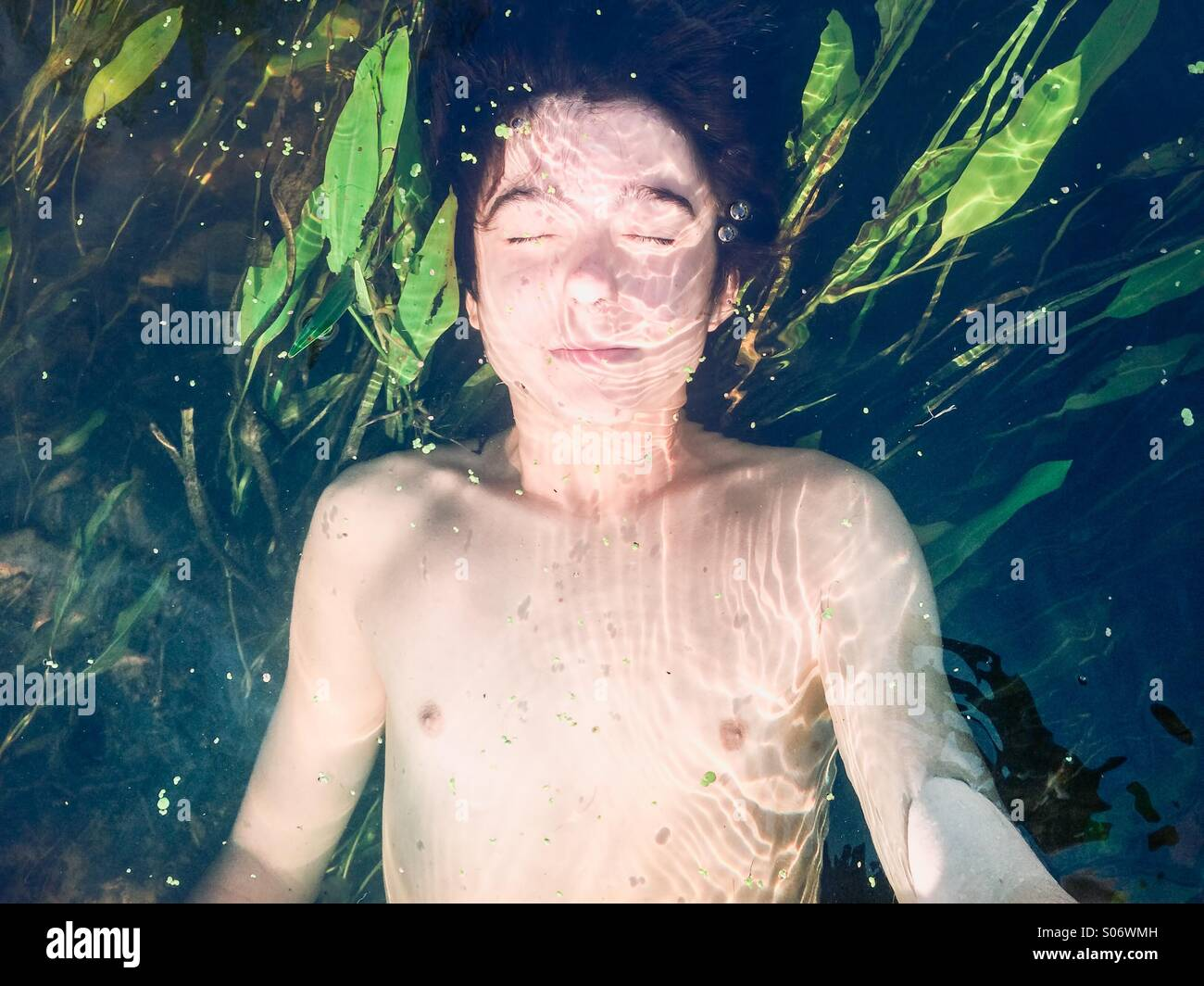Boy submerged in a pure river with lush greenery - Stock Image