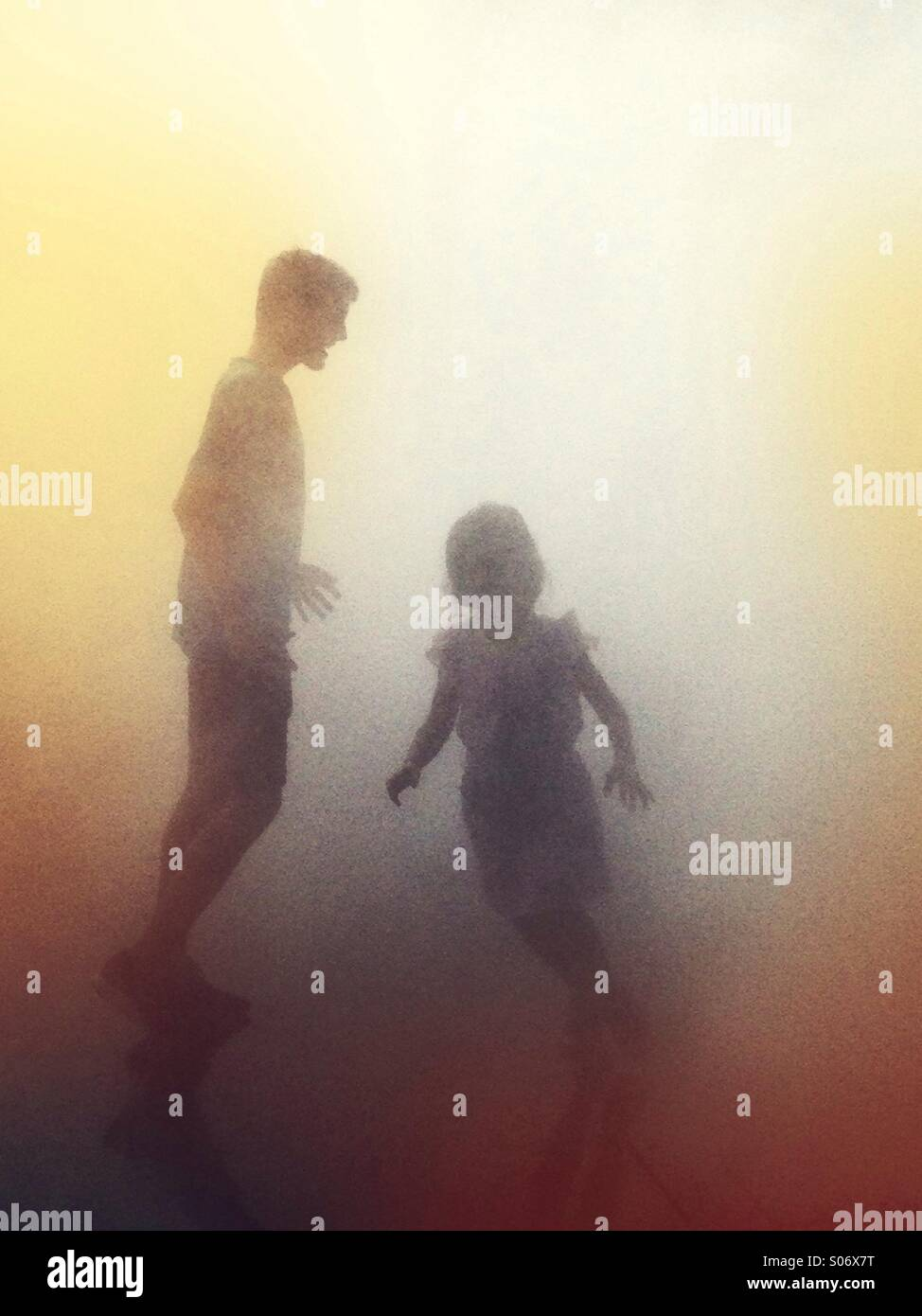 Man and child crossing paths in the mist - Stock Image