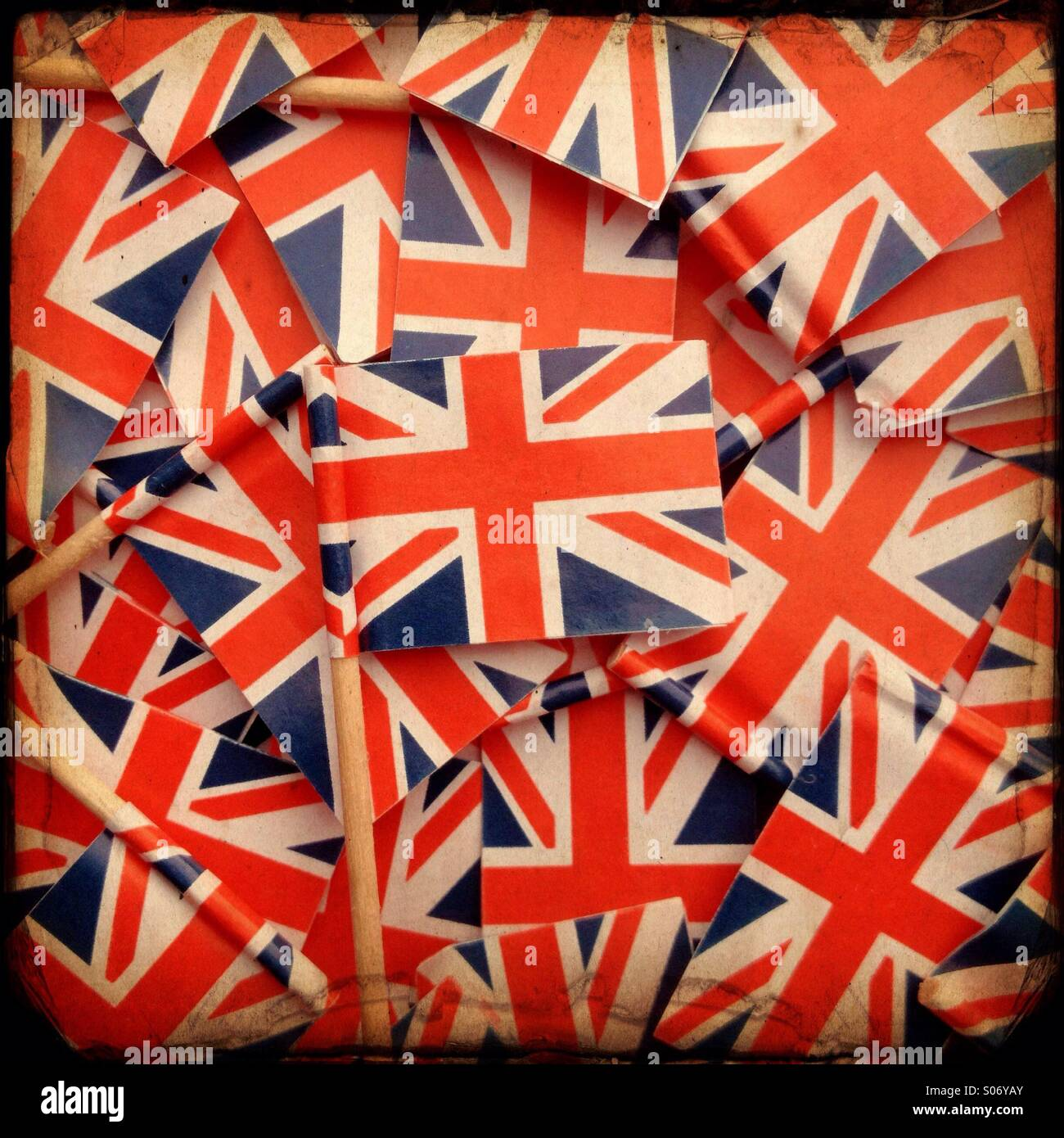 Union Jack cocktail sticks arranged to make a background with a vintage texture effect - Stock Image