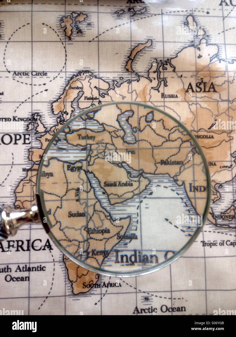 Magnifying glass magnifying a world map - Stock Image