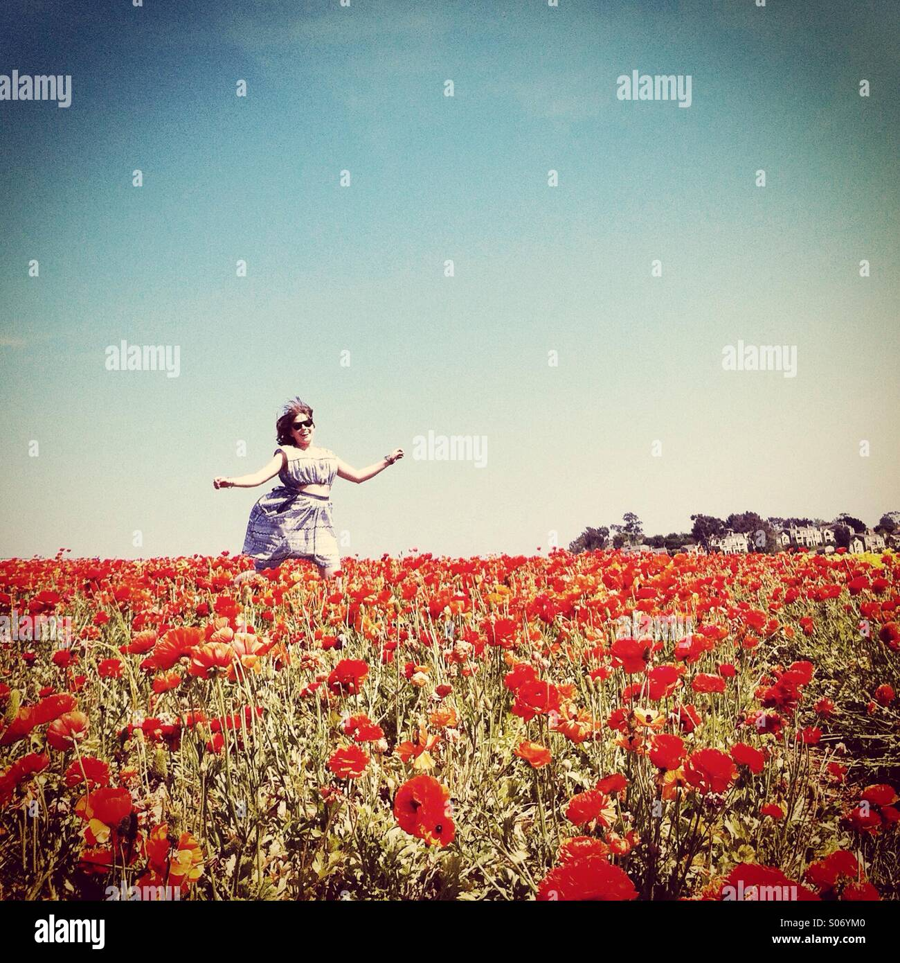 Girl dancing in field of poppies - Stock Image