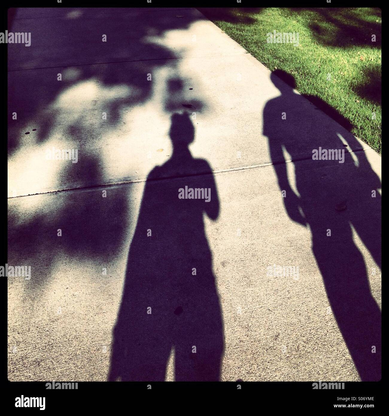 Man and woman shadows on sidewalk - Stock Image