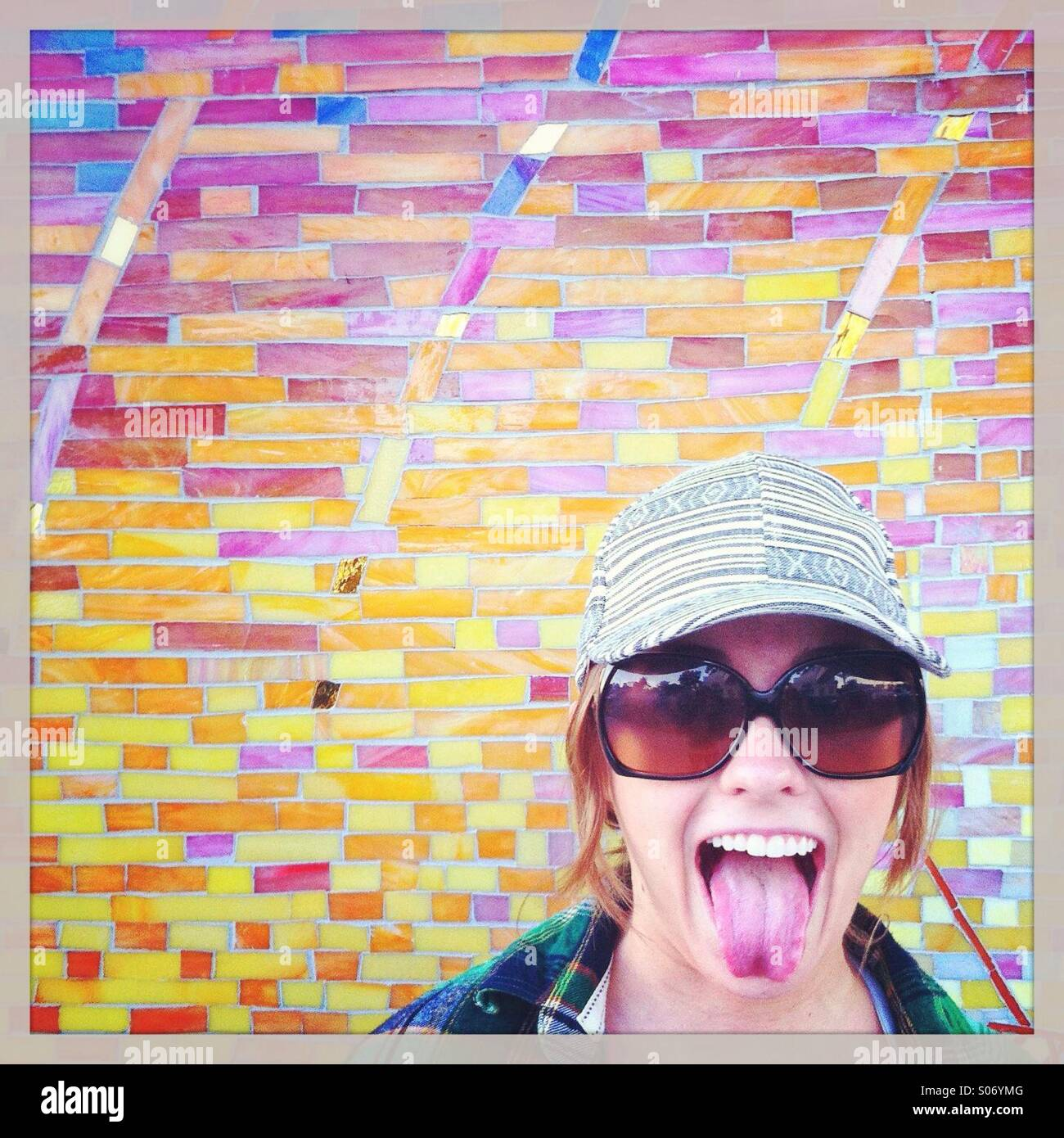 Woman sticking her tongue out in front of mosaic wall - Stock Image