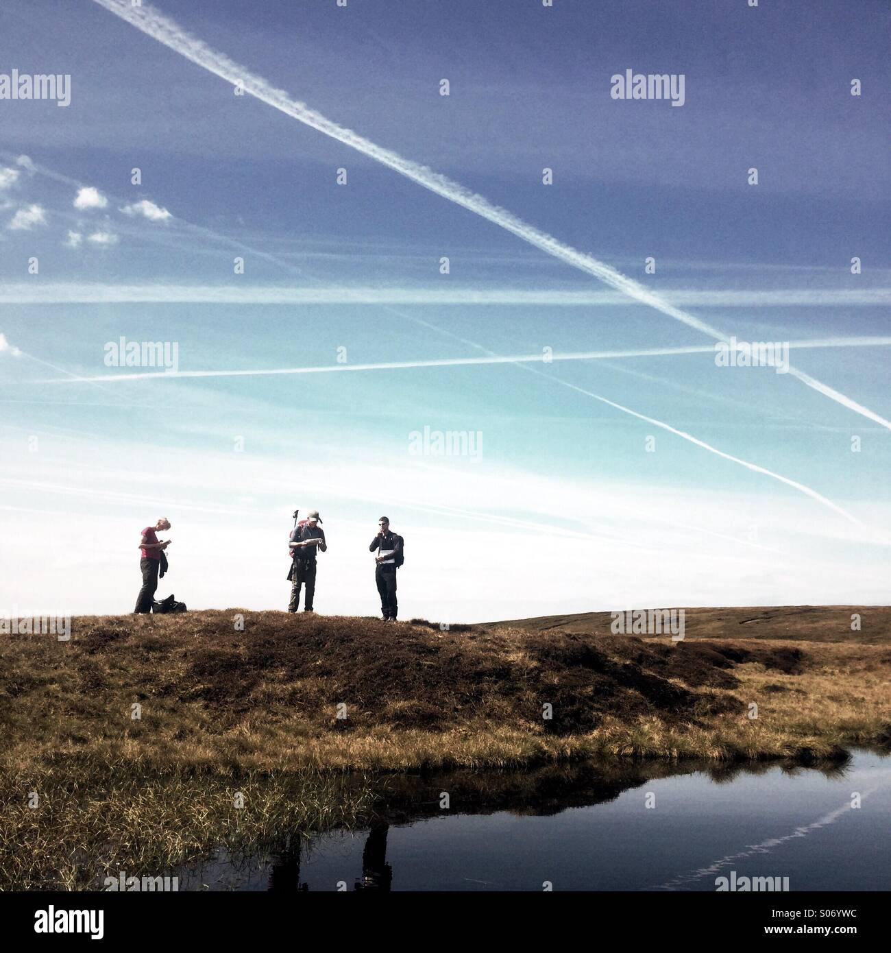 Three hill walkers on moorland in Yorkshire - Stock Image