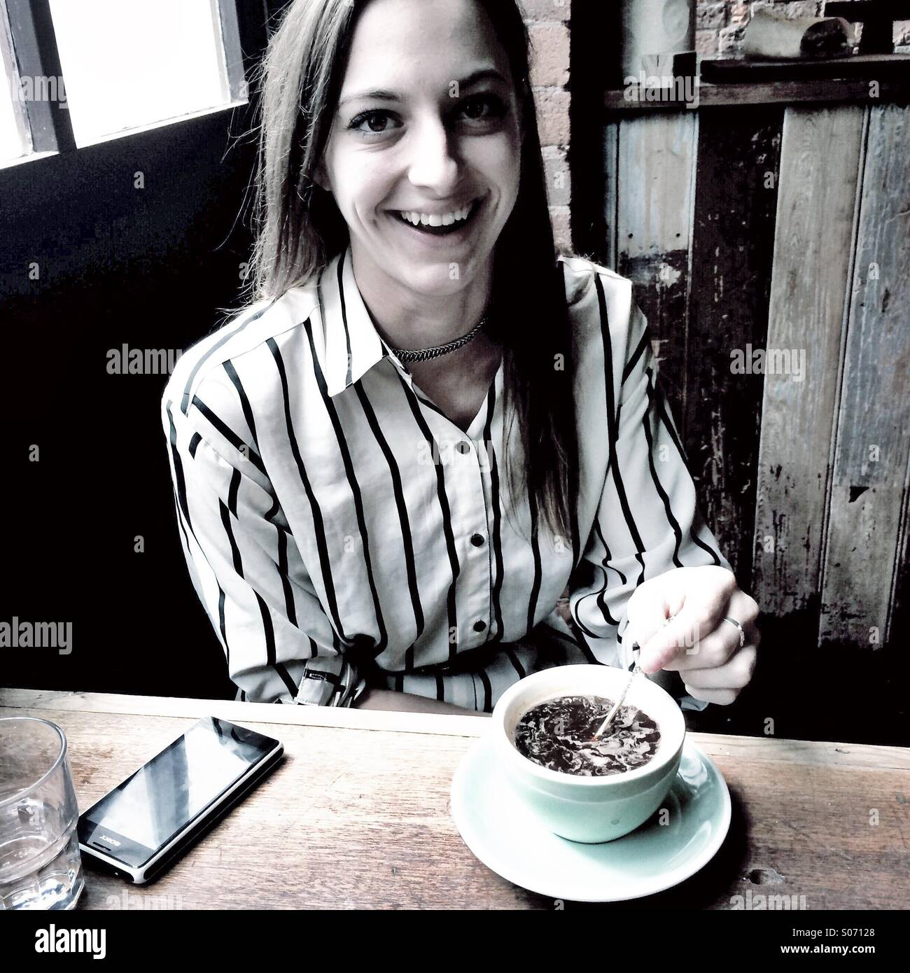 A young woman smiling in a cafe - Stock Image