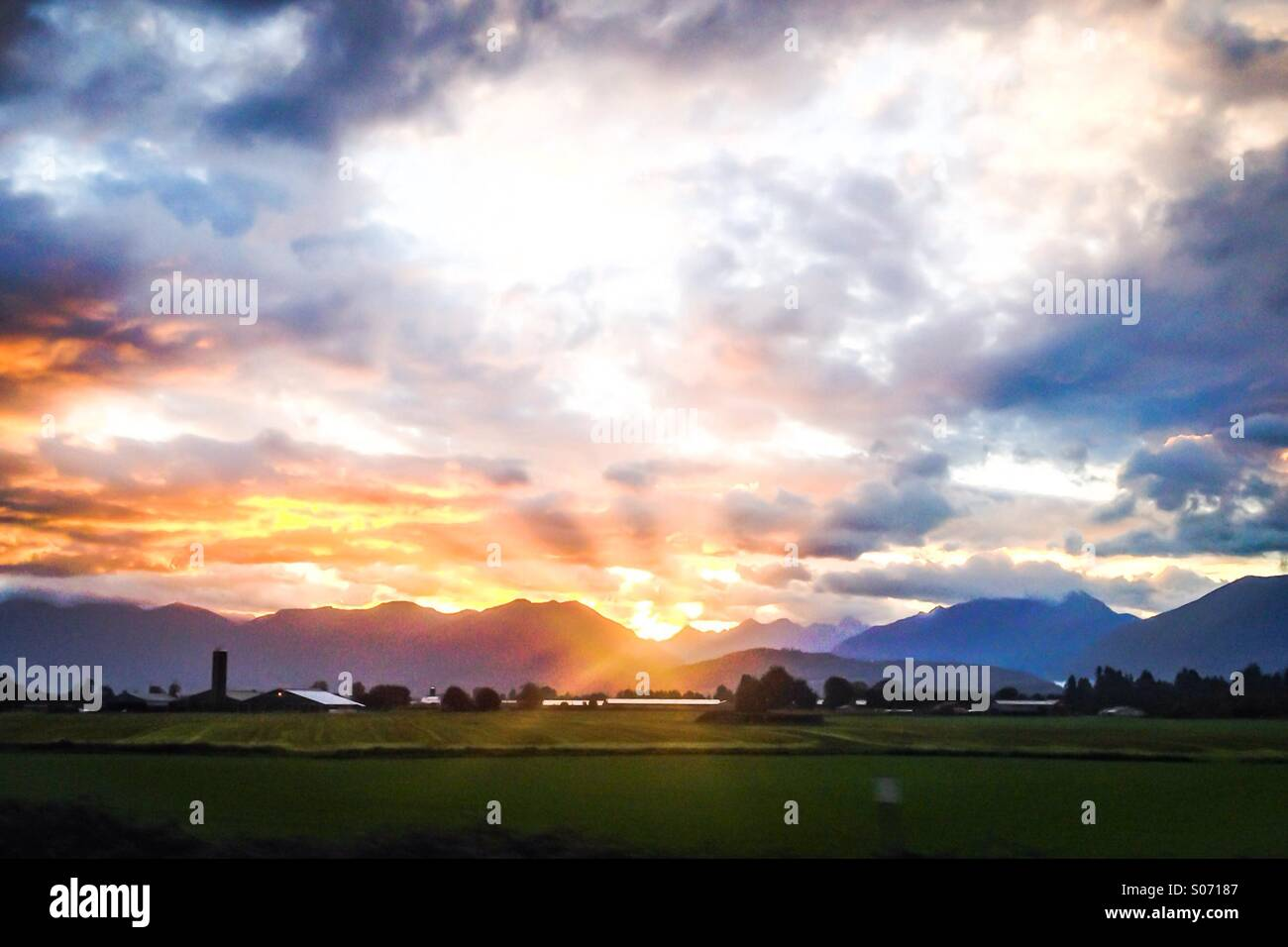 Sun rising amongst the clouds, over the mountains. The green pastures and farm getting the first lights of the day. - Stock Image