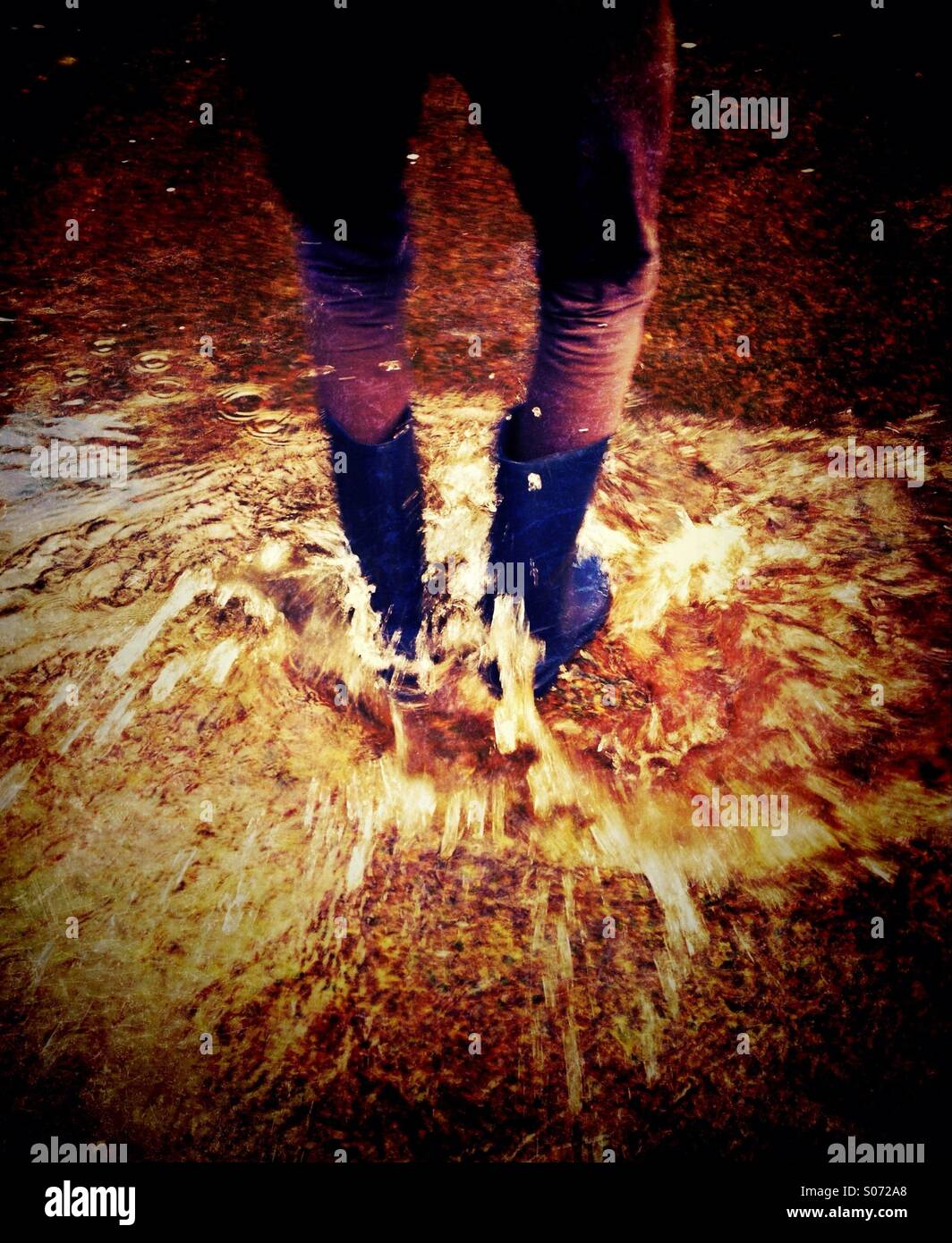 Young girl splashing in stream - Stock Image