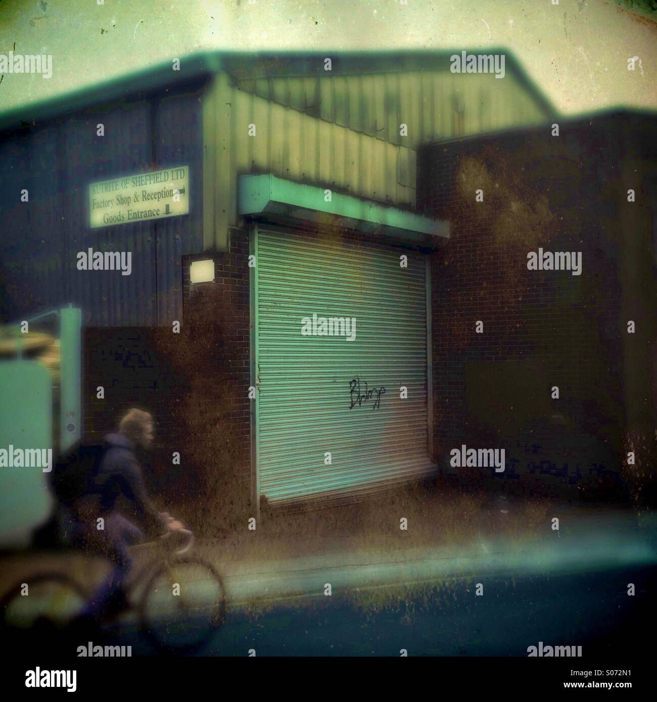 A man in a bike rides past a industrial unit - Stock Image