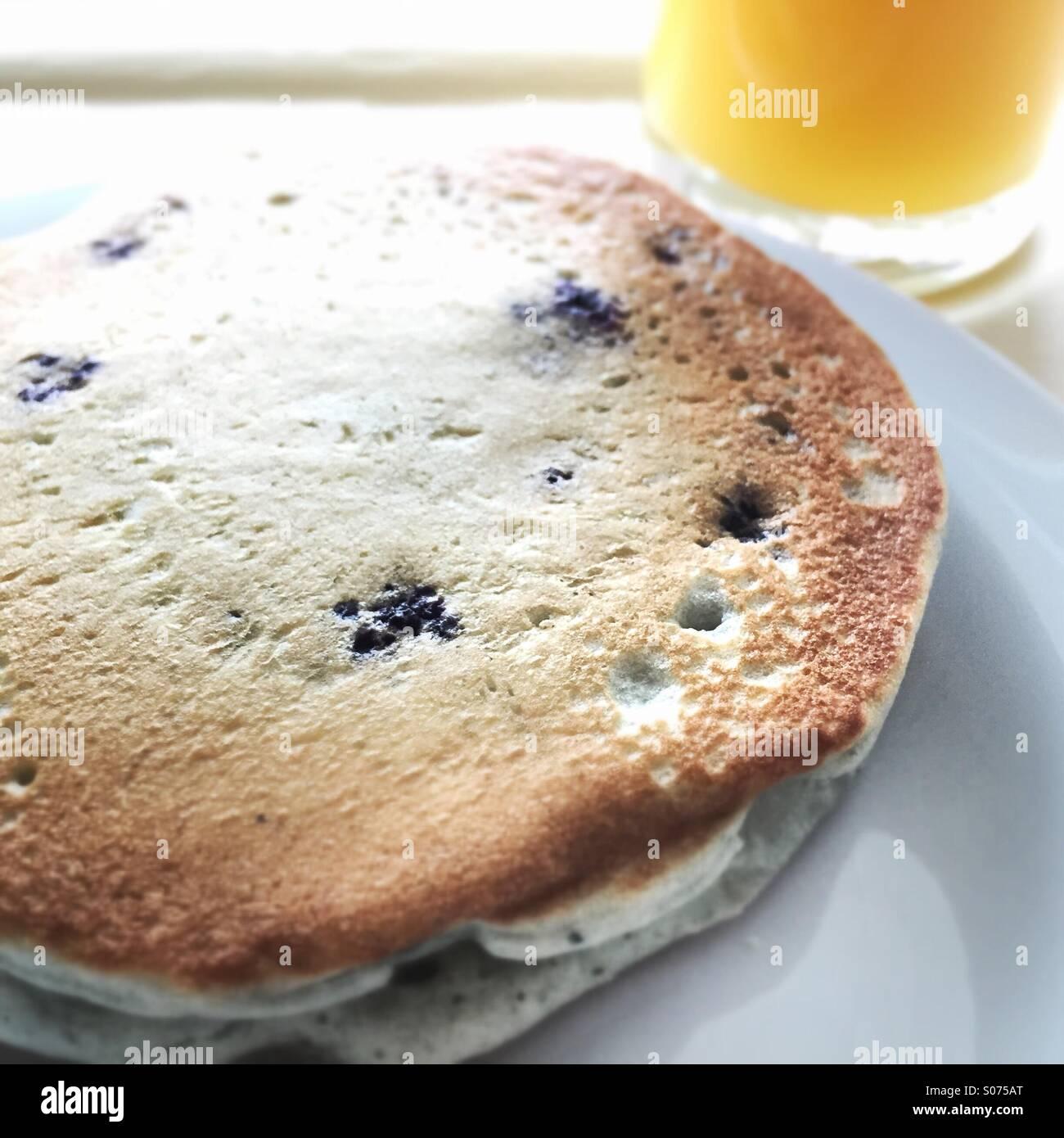 Blueberry pancakes and orange juice. - Stock Image