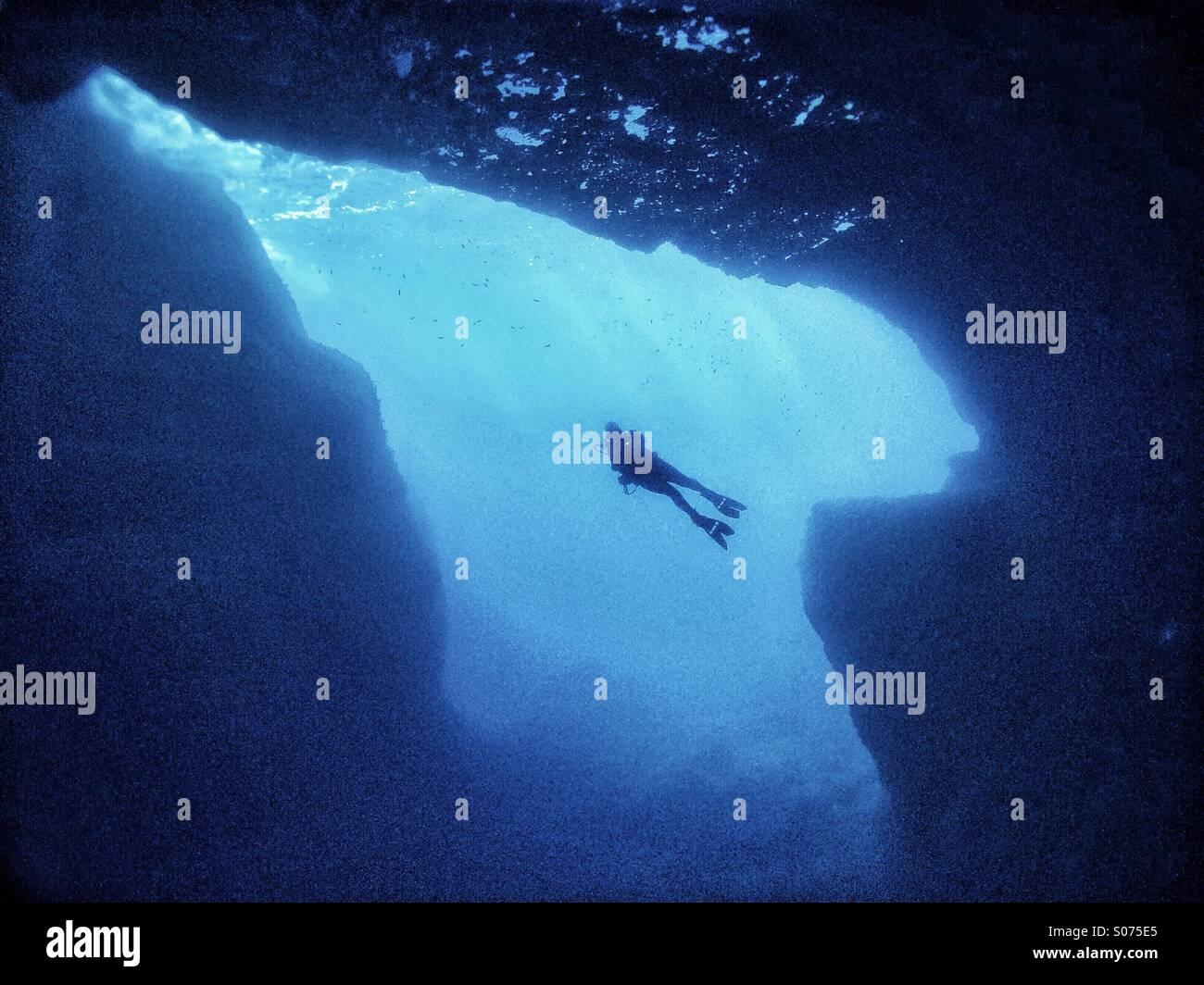 Mature male scuba diver swimming across underwater cavern - Stock Image
