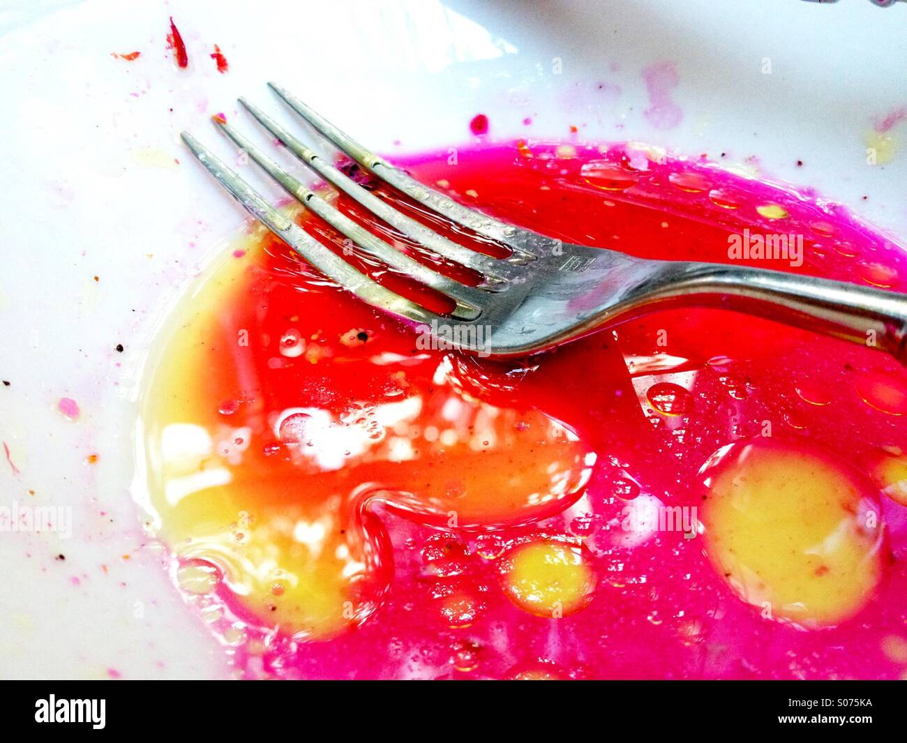 Fork with juice from beet salad - Stock Image