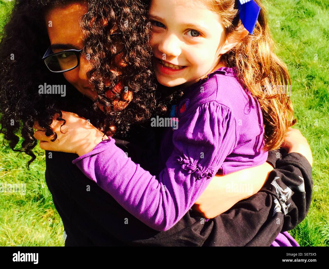 13 year old girl and 5 year old girl hugging - Stock Image
