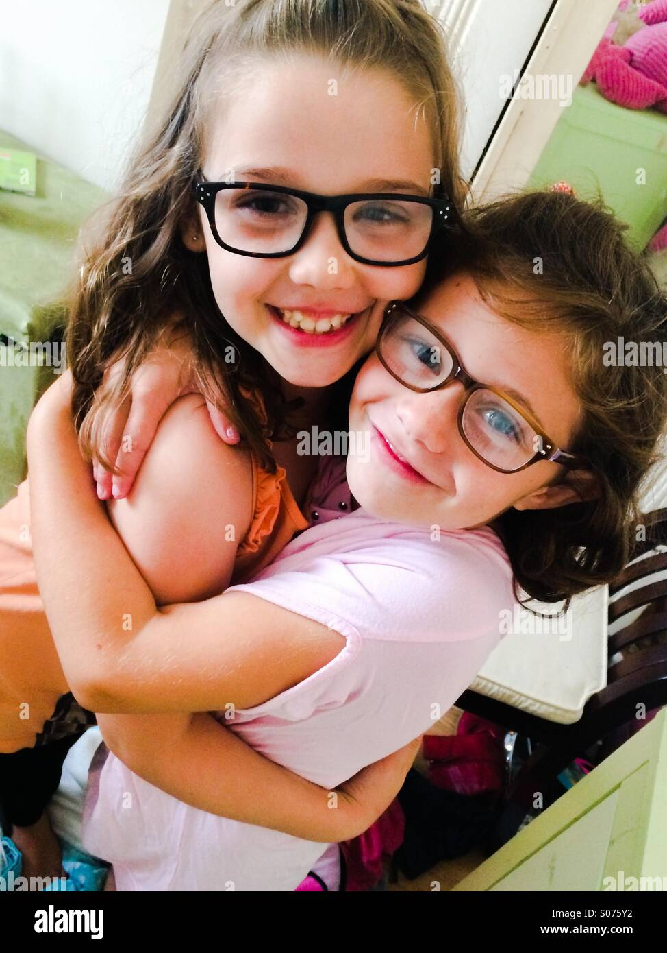 Two 6 year old girls wearing glasses - Stock Image