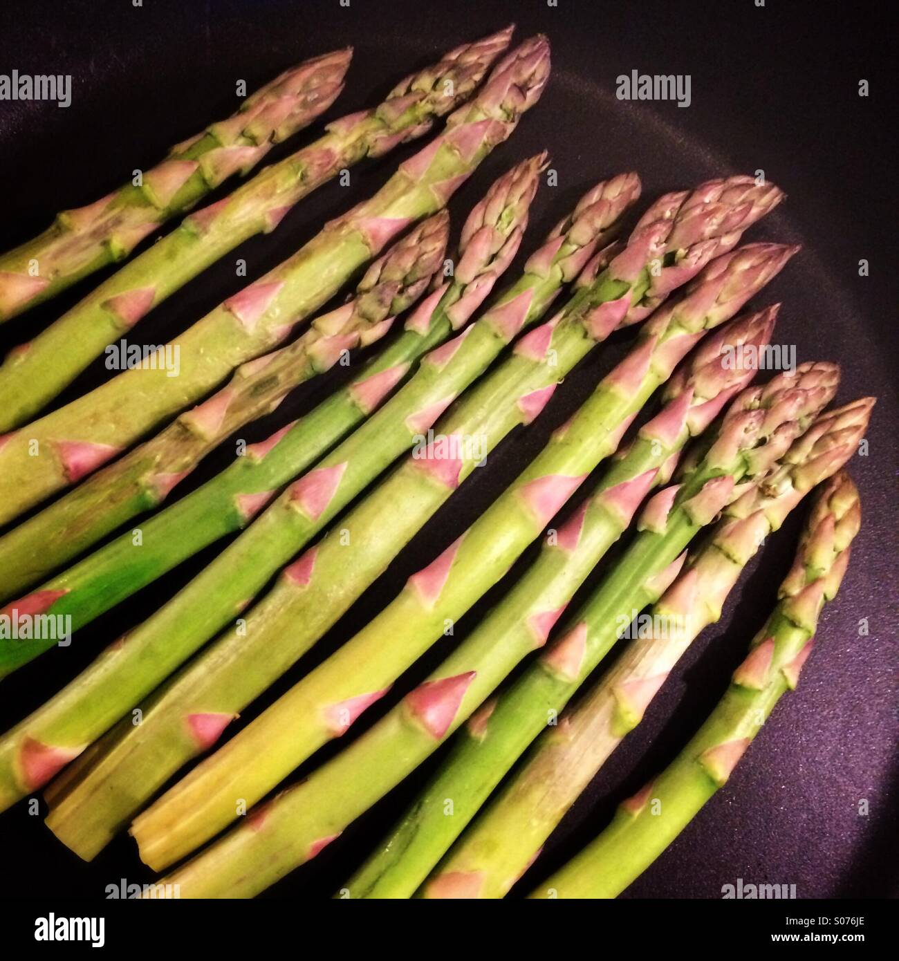 Dry-roasted asparagus in teflon pan - Stock Image