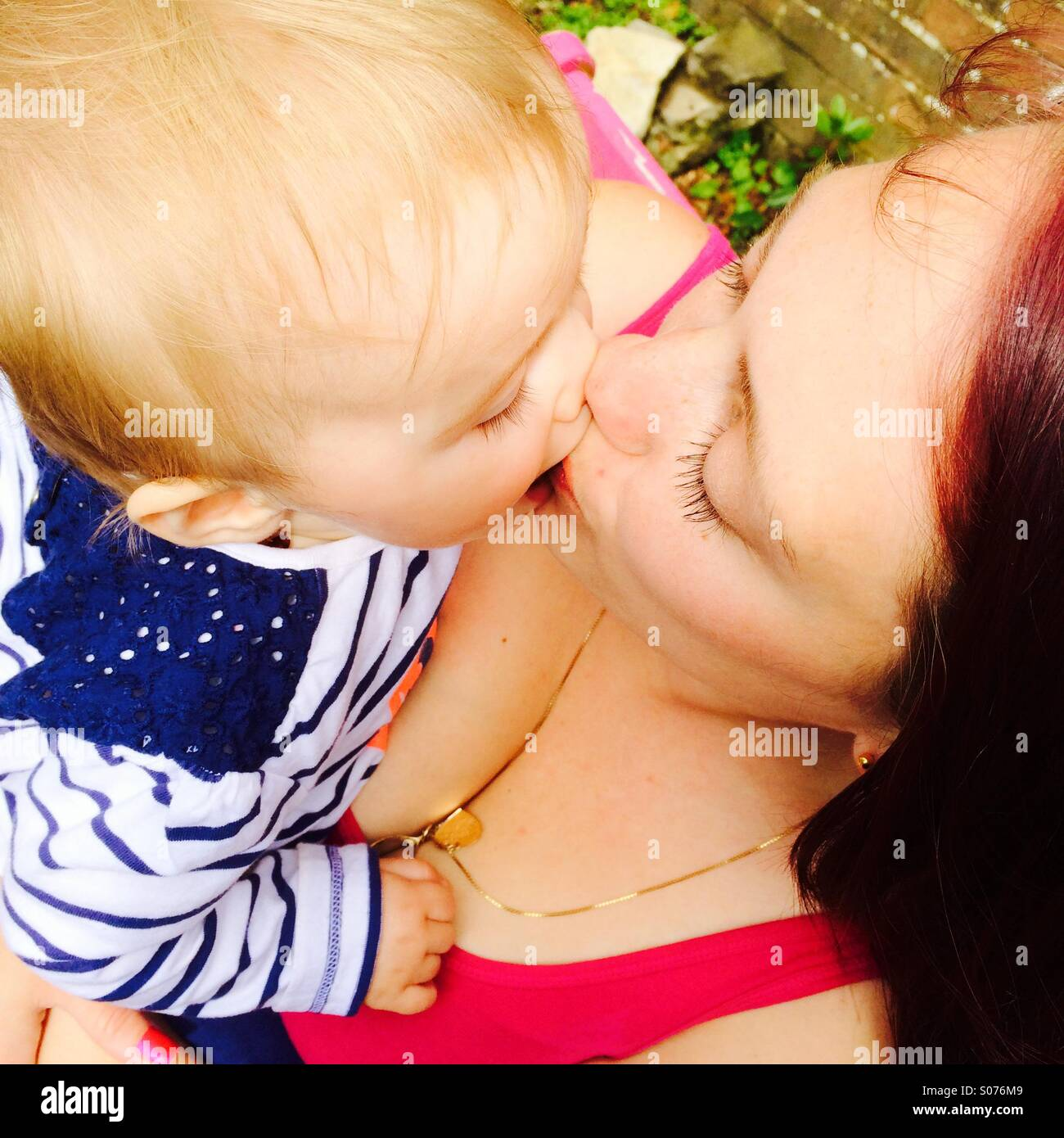 Mother and baby kissing - Stock Image