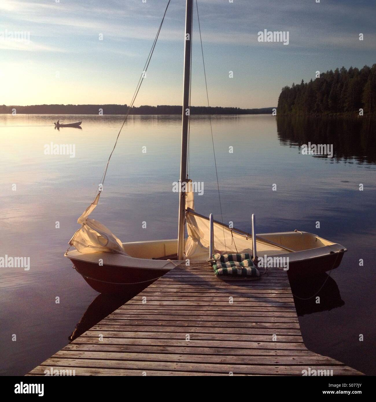 A sailing boat and a fishing boat on an idyllic Nordic lake in the north of Finland - Stock Image