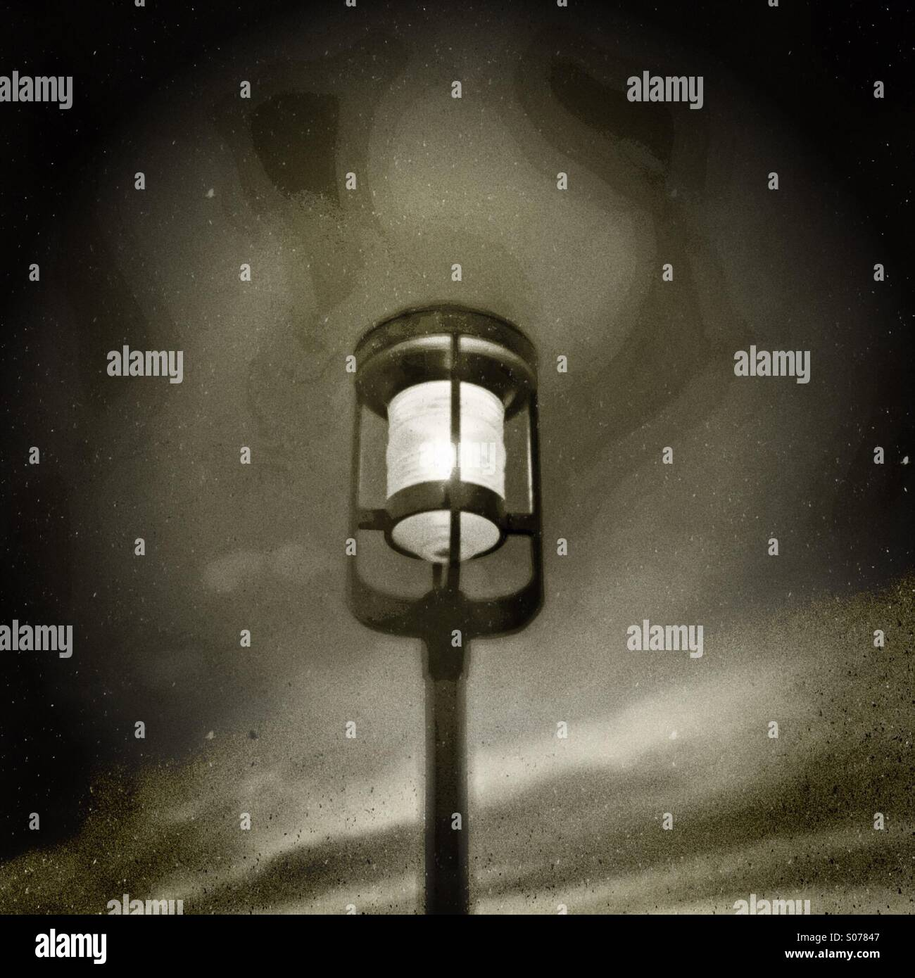 A lone lamp lights a parking lot. - Stock Image