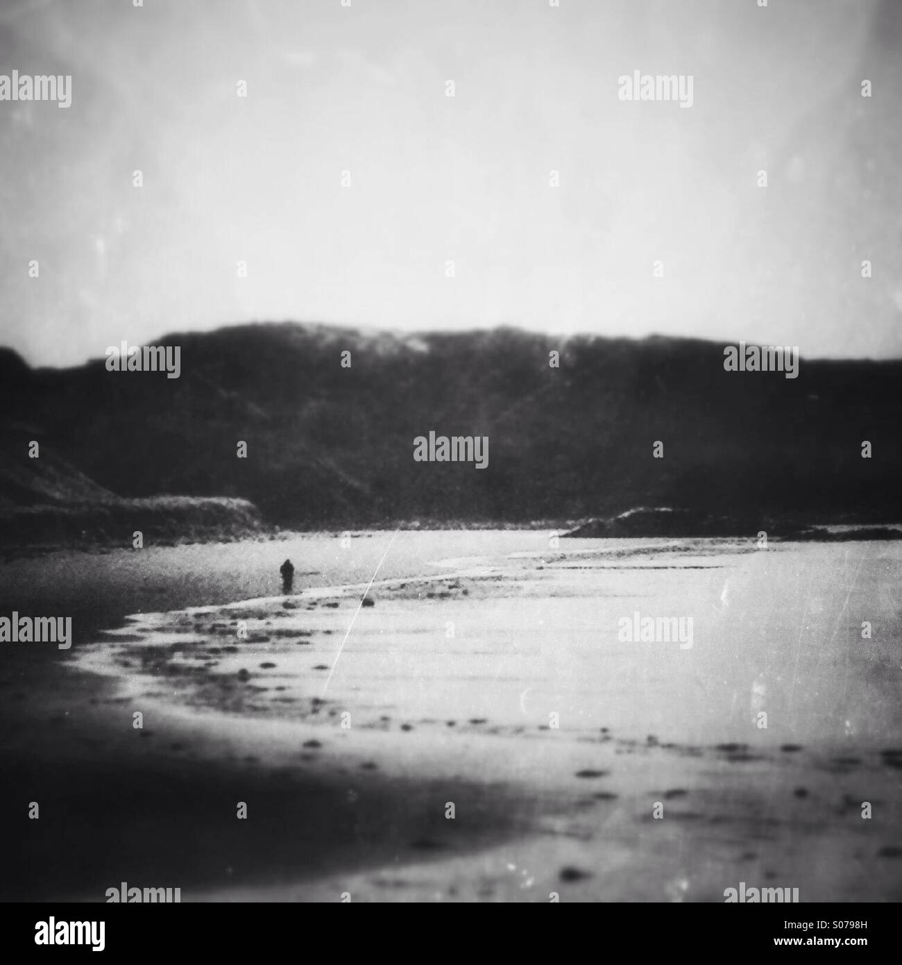 Lone person walking along the shore. Old style effects and textures added. - Stock Image