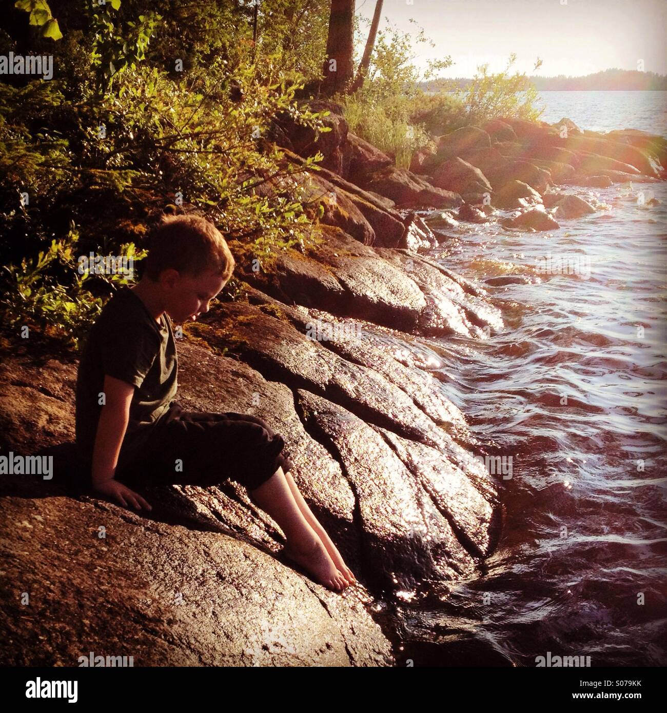 A young boy dipping his toes in the water at a Nordic Scandinavian summerhouse lake - Stock Image
