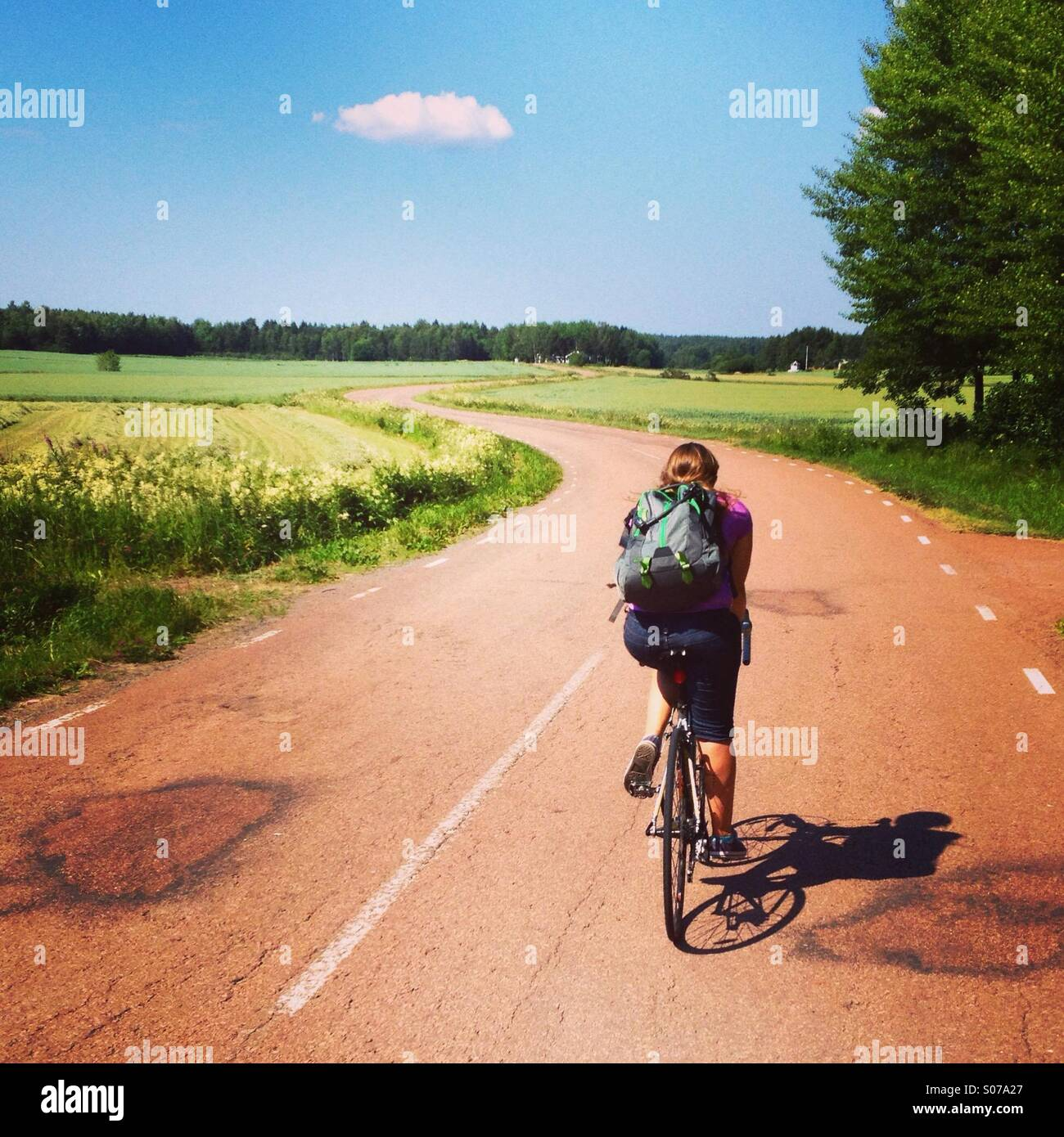 A woman on a cycling holiday on a snaking traditional red road in the Nordic Finnish archipelago of Åland - Stock Image